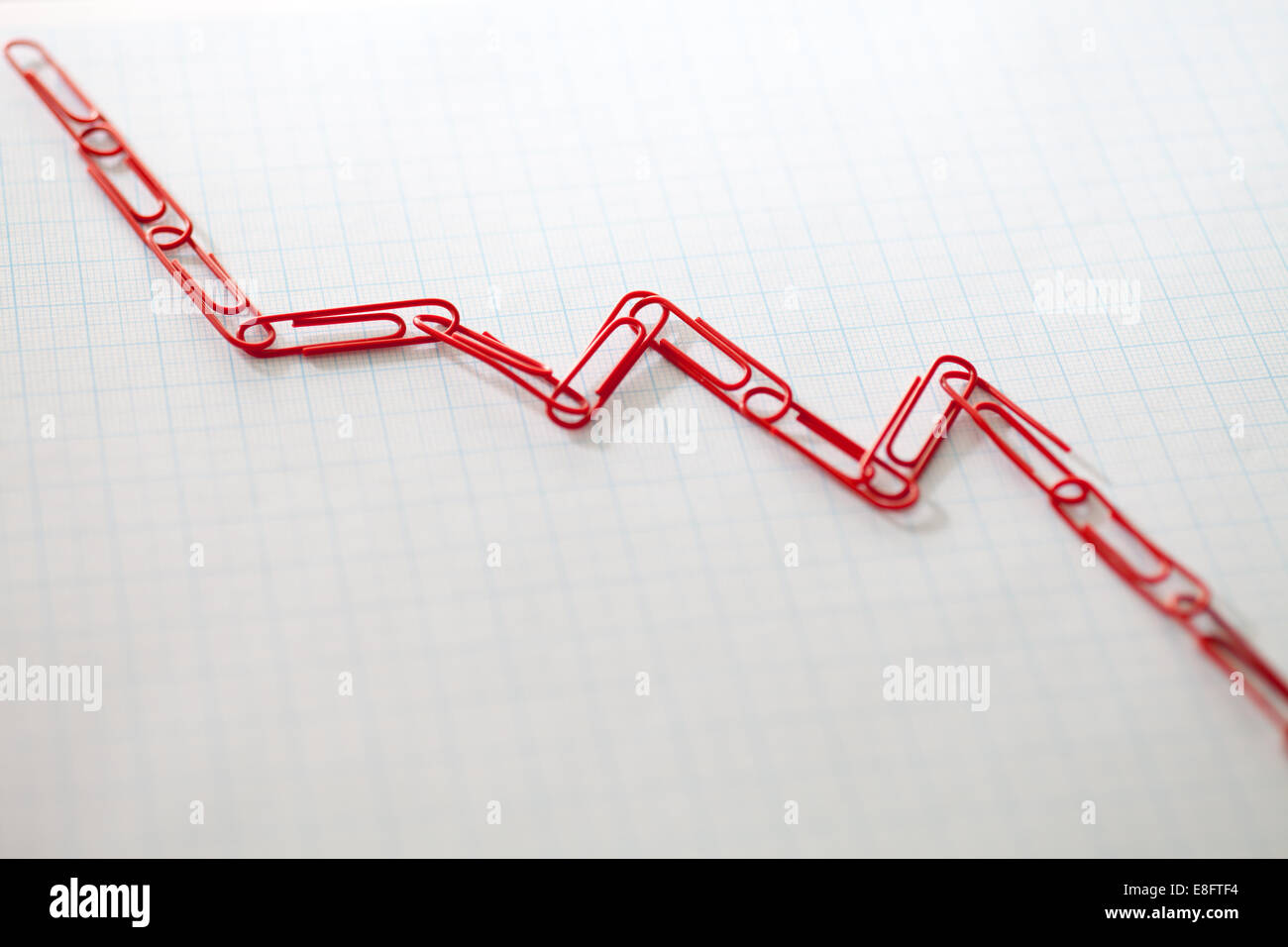 Linked paper clips on graph paper - Stock Image