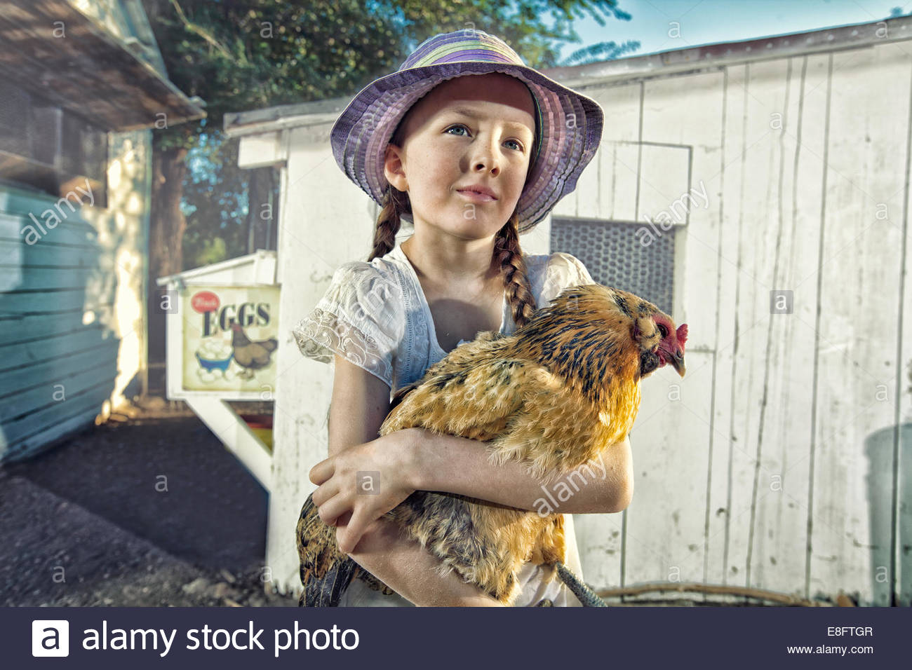 Portrait of a girl on a farm carrying a chicken - Stock Image