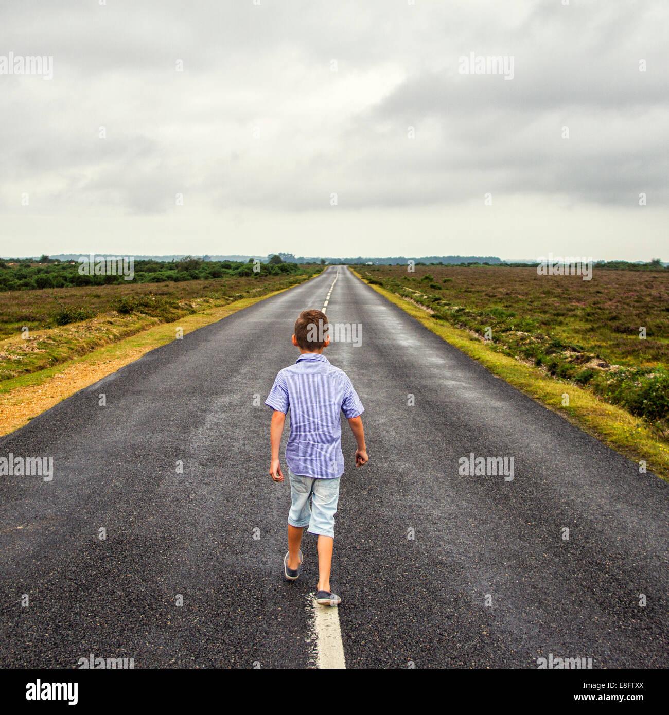 Lone boy walking down long road - Stock Image