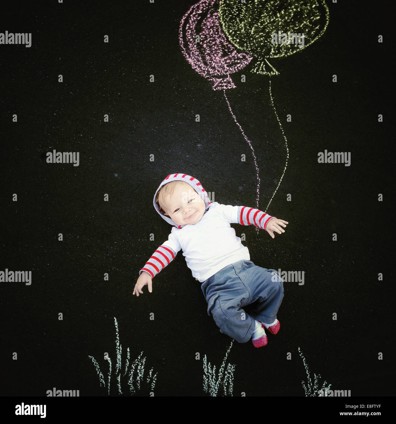 Baby boy with chalk drawing of balloons - Stock Image
