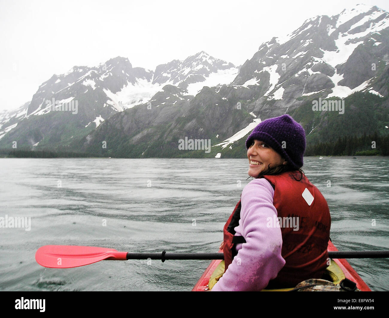 Woman kayaking near glaciers in Kenai Fjords National park, Alaksa, America, USA - Stock Image