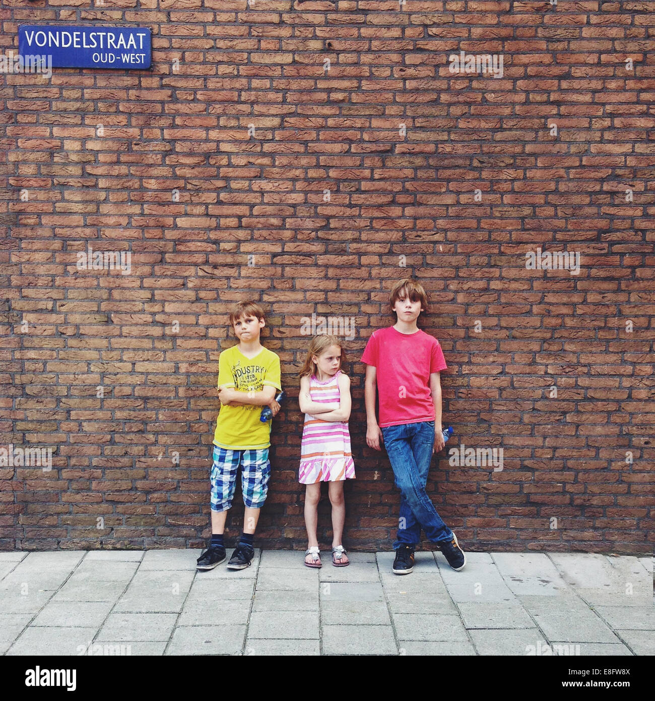 Three children (10-11, 12-13) standing in front of brick wall - Stock Image