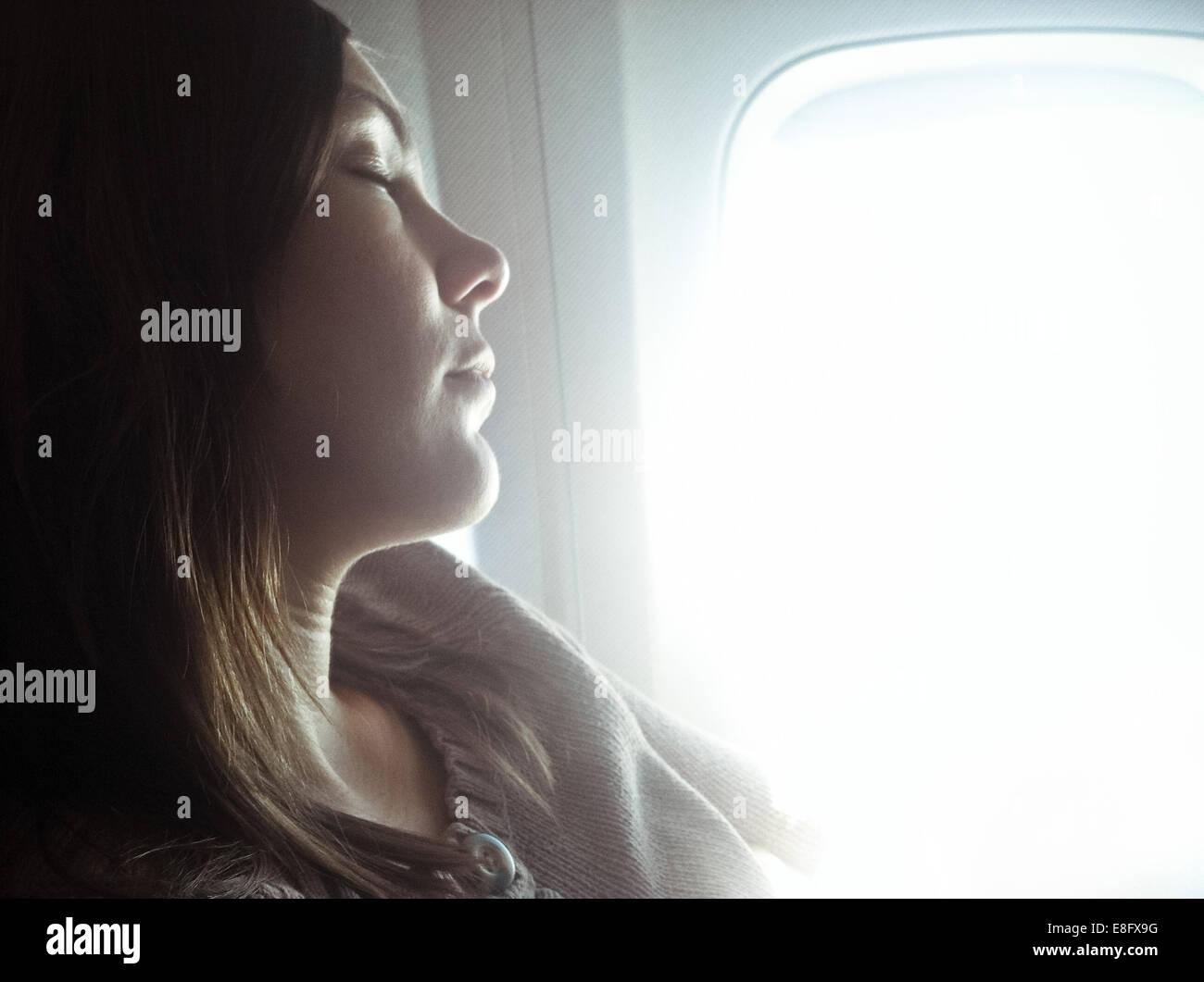 USA, Colorado, Denver County, Denver, View of woman sleeping on plane - Stock Image