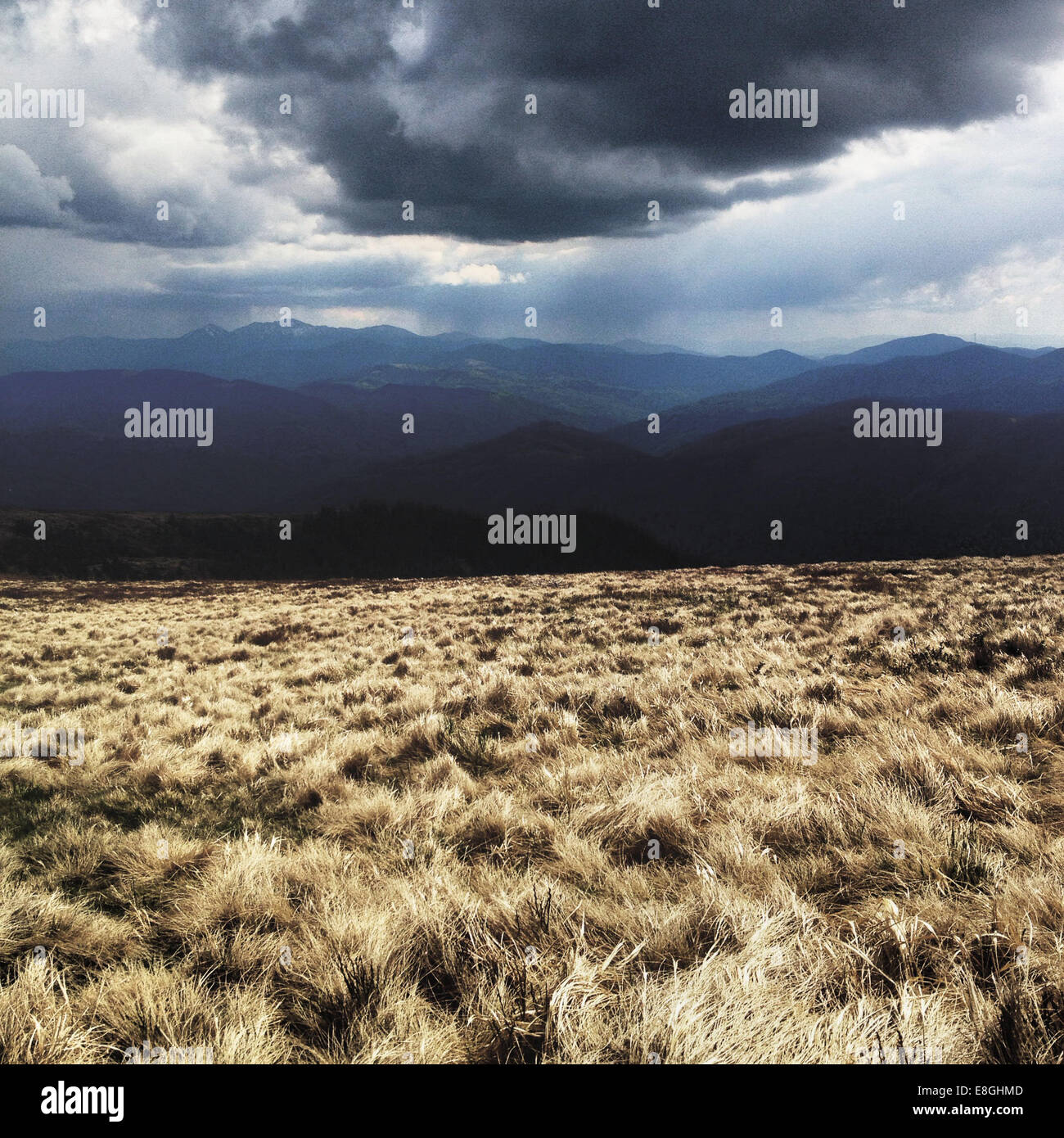 Heavy cloud over field and mountains - Stock Image