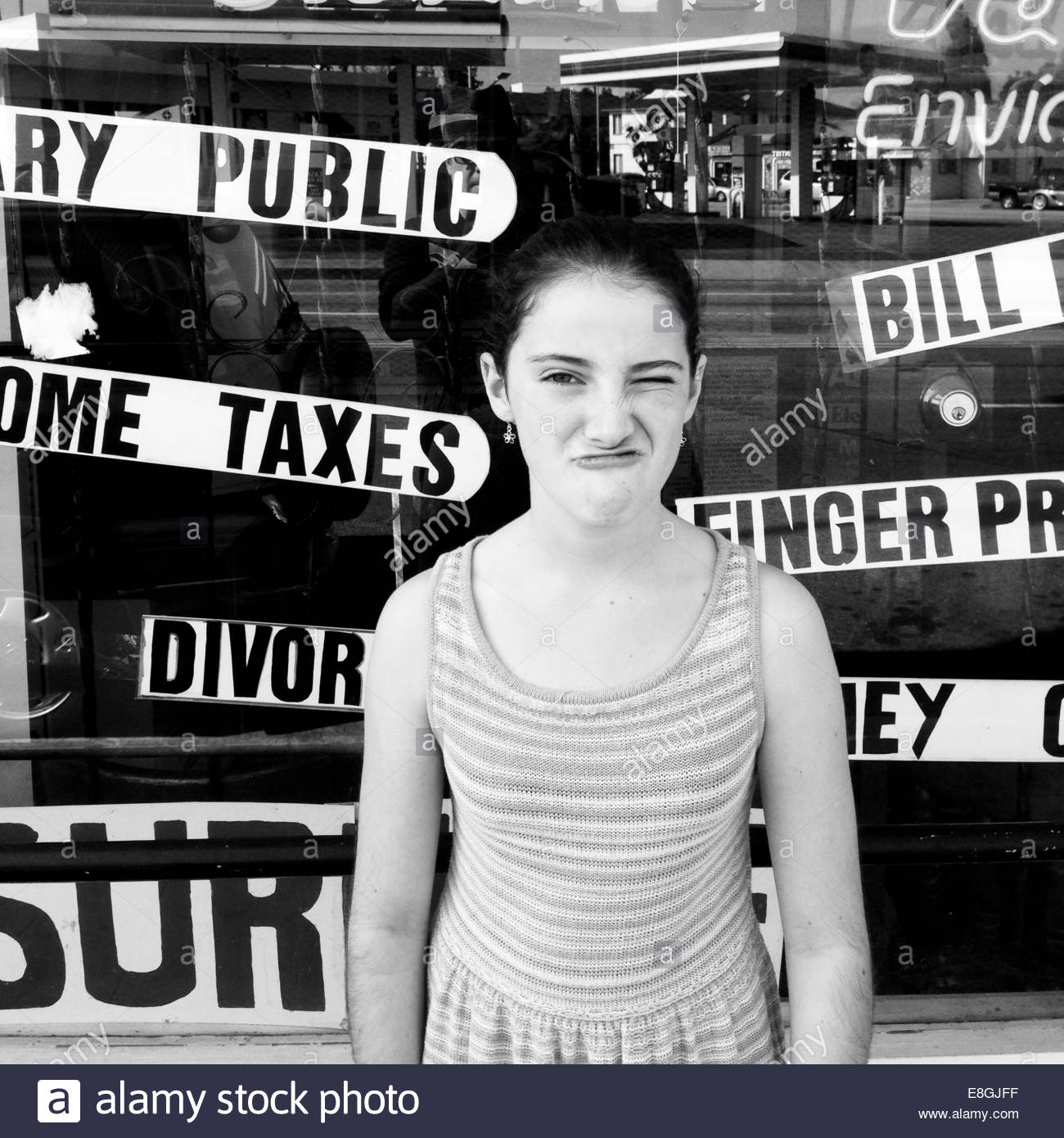 Girl making cheeky face in front of shop window - Stock Image