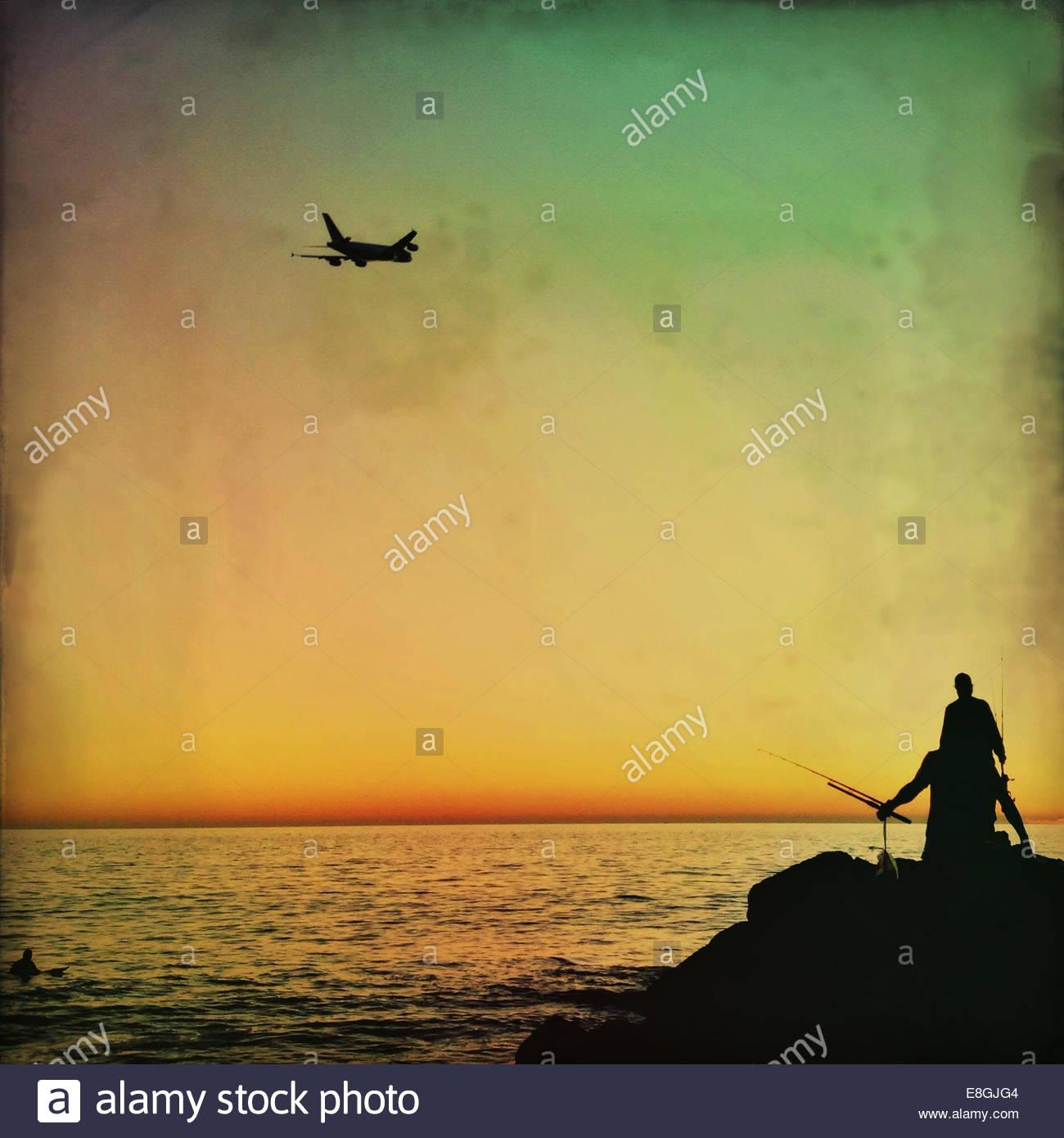 Airplane above fishermen - Stock Image