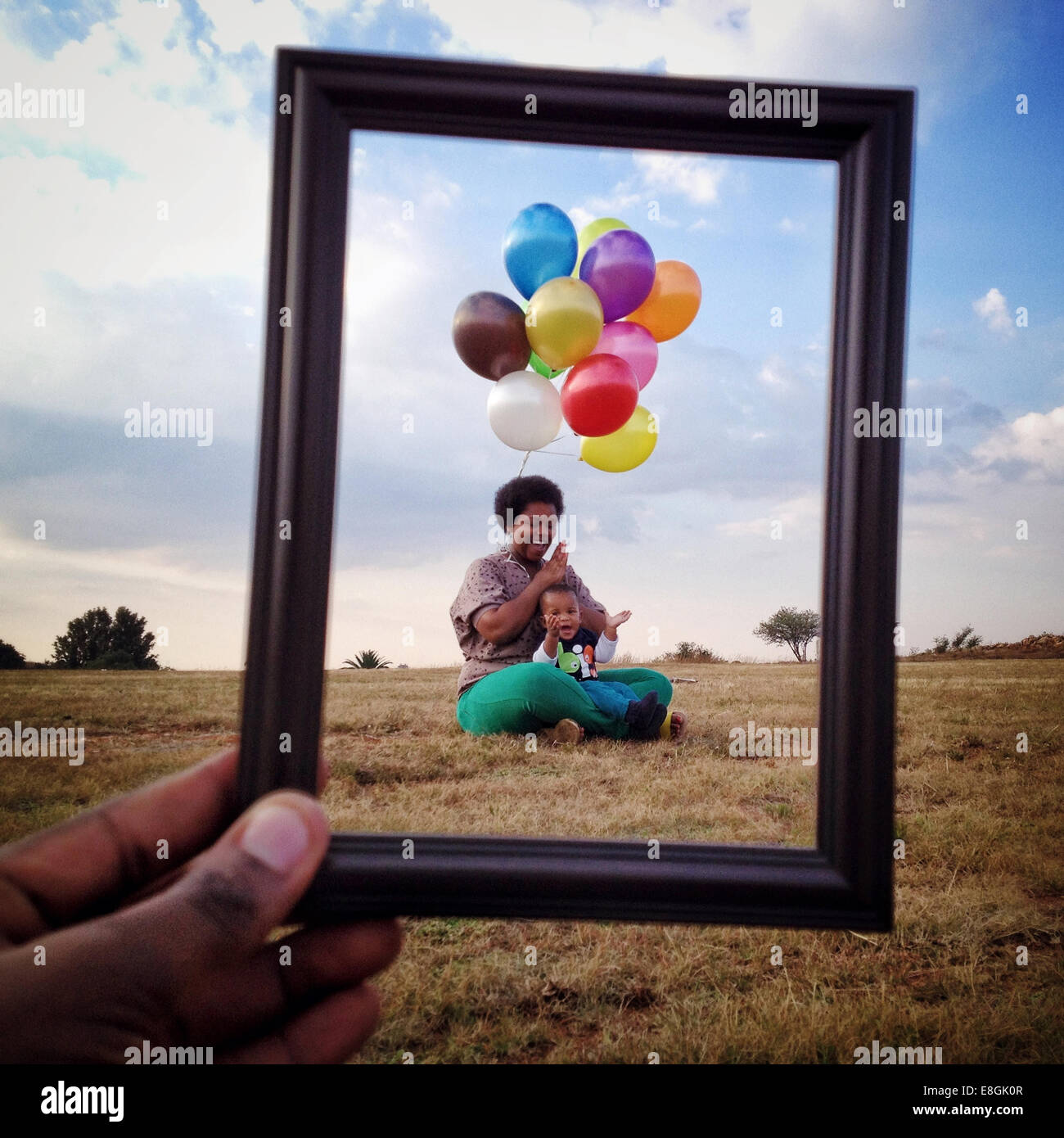 South Africa, Gauteng, Johannesburg, Roodepoort, Mother and son (12-17 months) sitting in meadow with bunch of colorful - Stock Image
