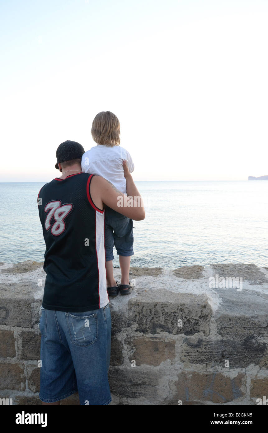 A Boy And His Father Watching The Ocean From A Brick Wall - Stock Image