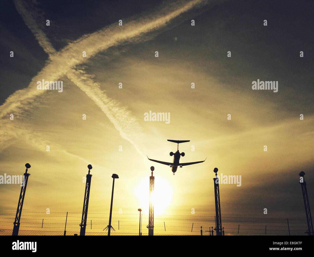 Silhouette of landing airplane - Stock Image