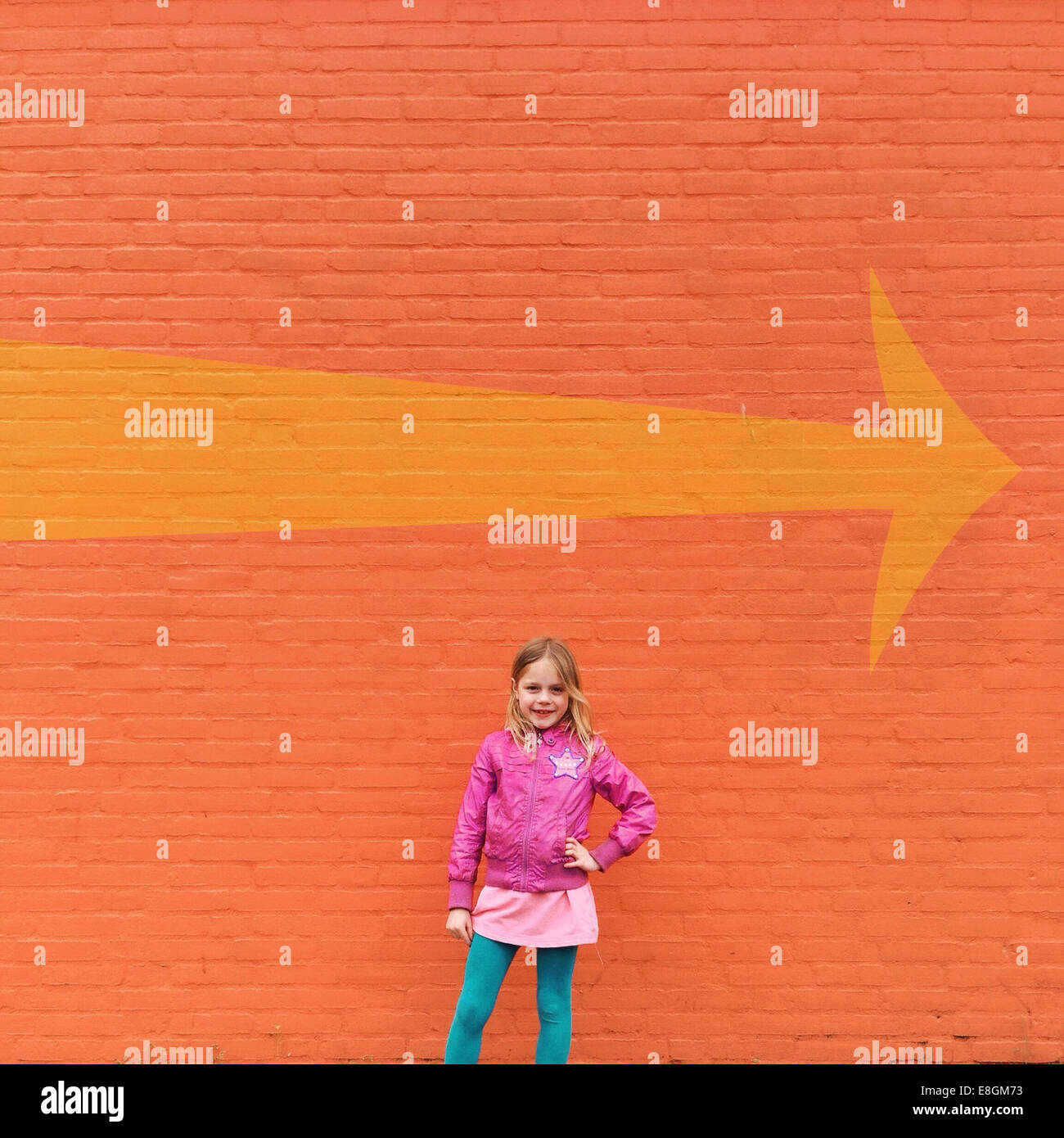 Portrait of girl (12-13) standing in front of orange wall - Stock Image