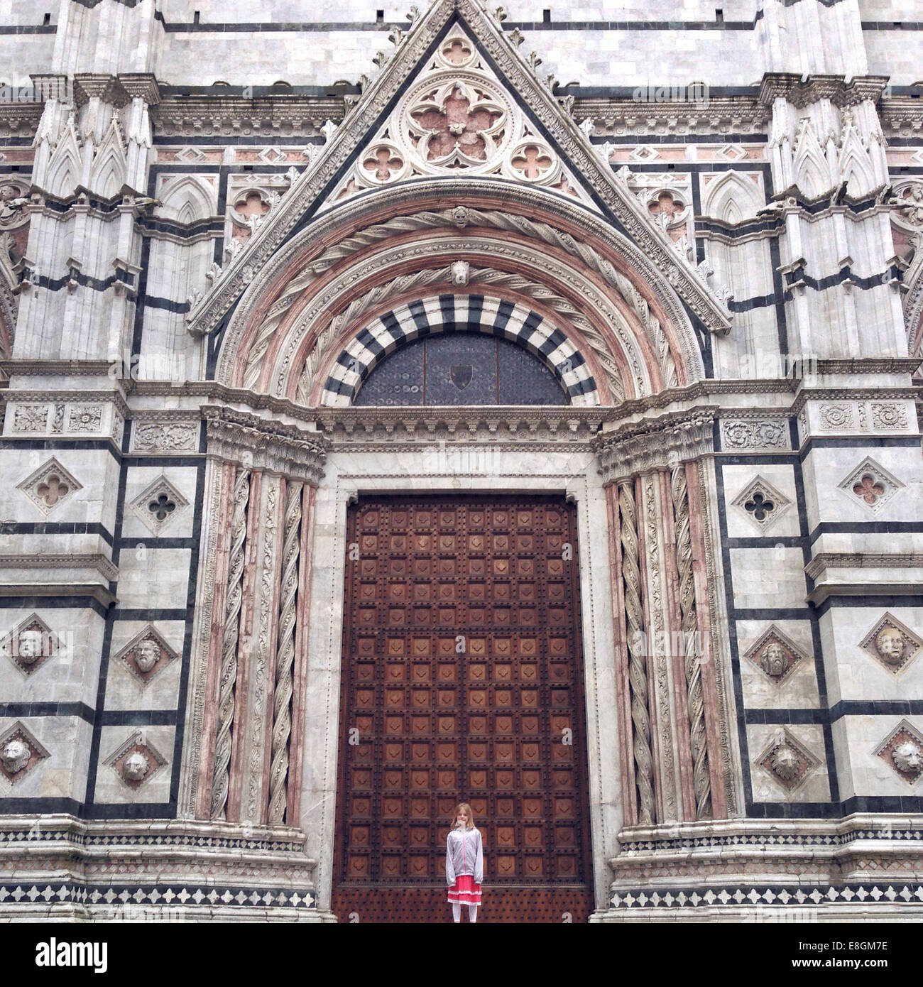Italia, Tuscany, Siena, Girl (12-13) standing in front of cathedral - Stock Image