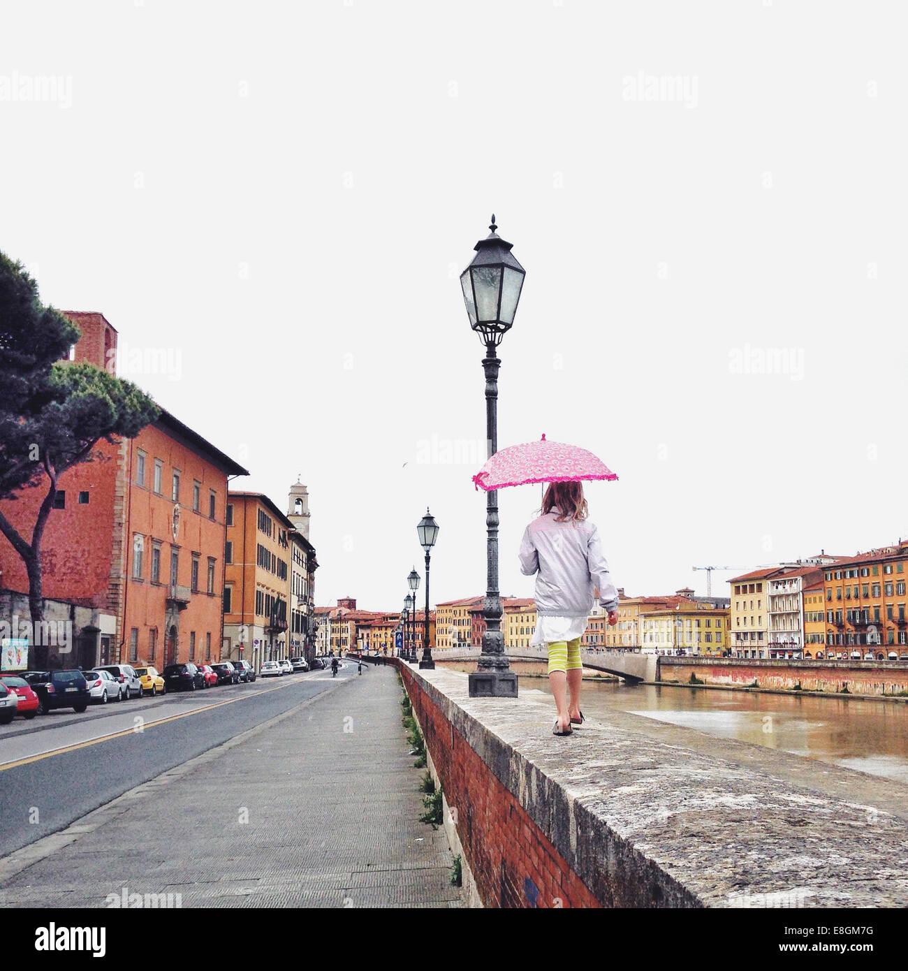 Italy, Tuscany, Pisa, Girl (12-13) with umbrella walking on ledge - Stock Image