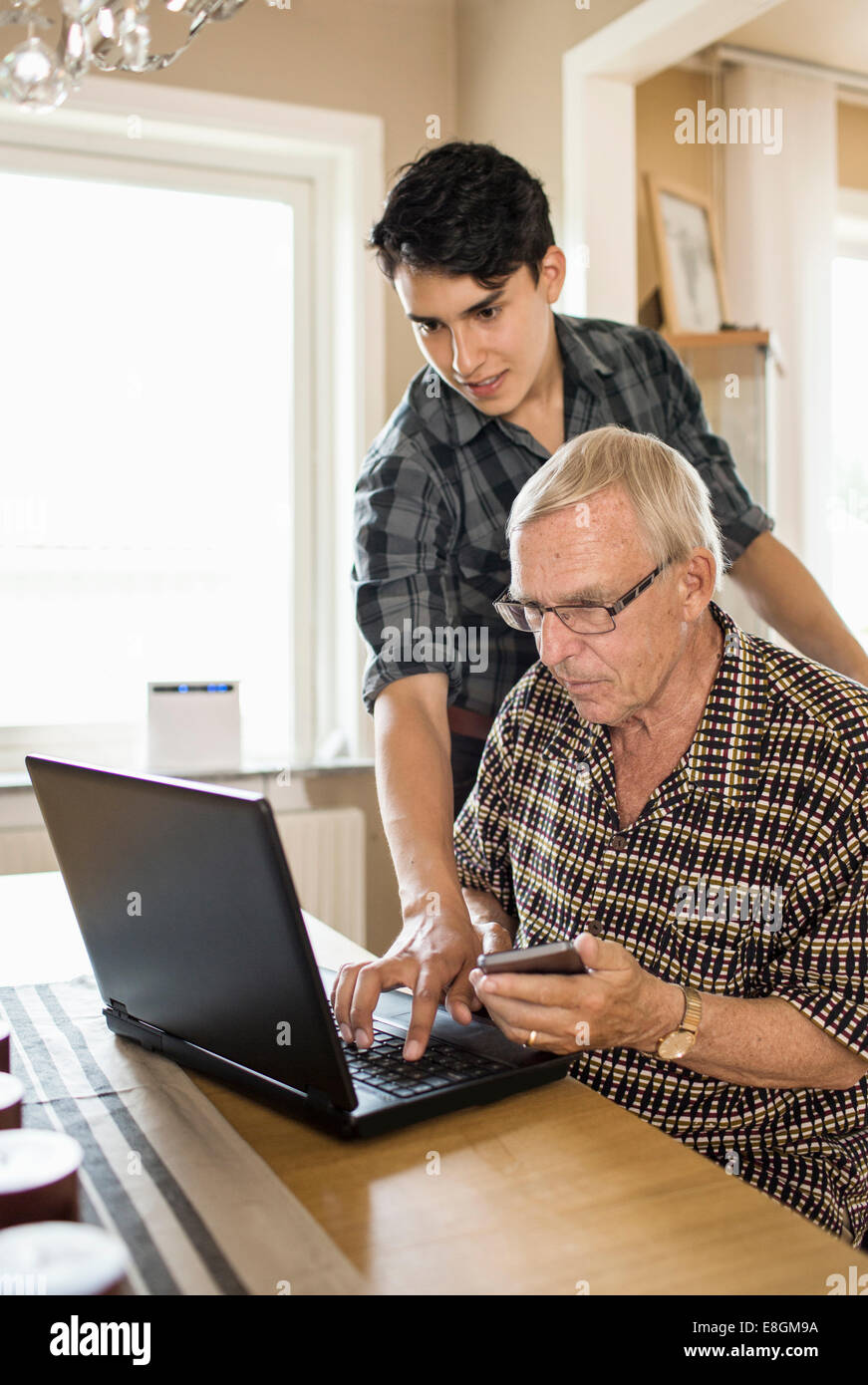 Grandson assisting grandfather in using laptop at home - Stock Image