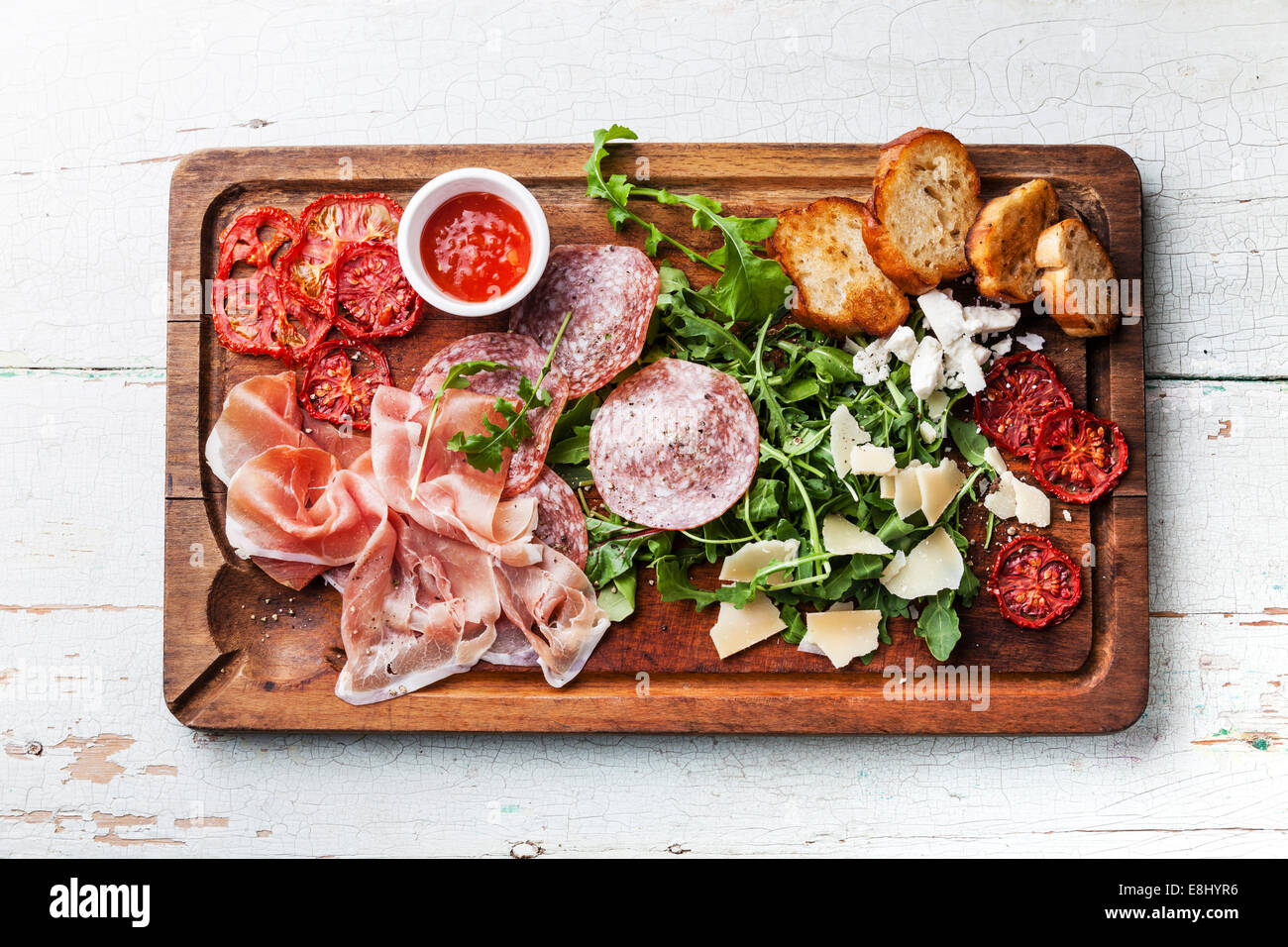 Cold meat plate and bread on wooden background - Stock Image