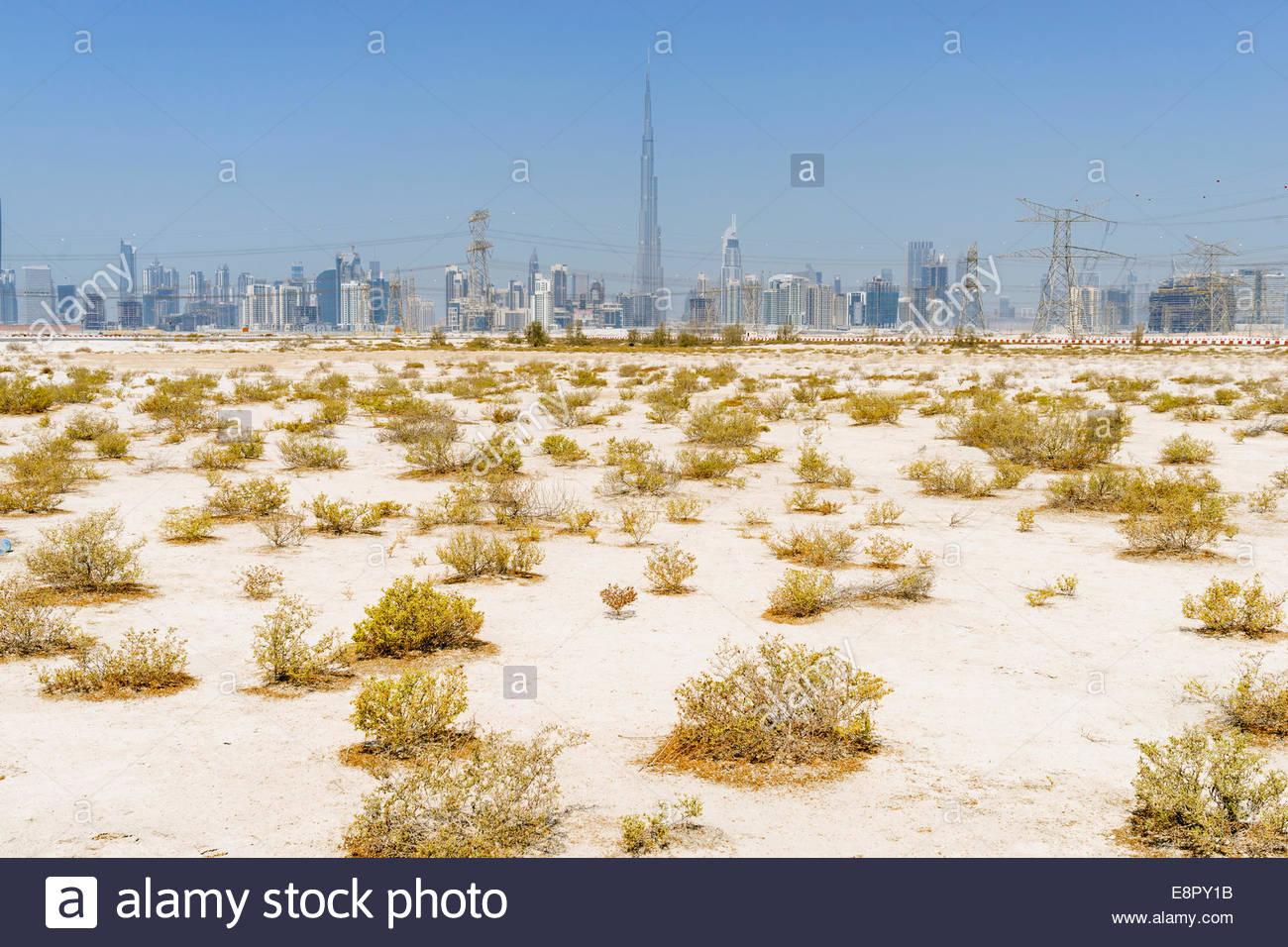 Skyline of skyscrapers and Burj Khalifa from the desert in Dubai United Arab Emirates - Stock Image