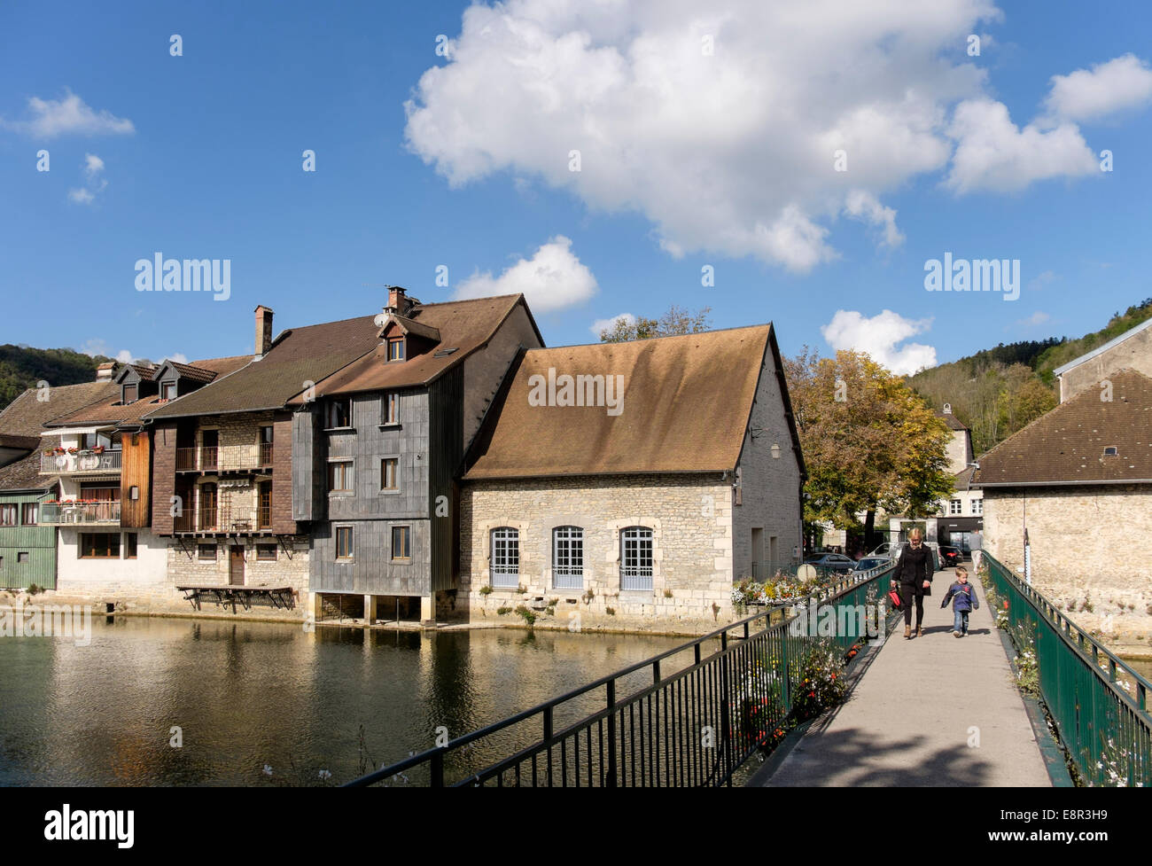 River Loue footbridge with quaint old houses in Loue Valley town of Ornans, Doubs, Franche Comte, France, Europe - Stock Image
