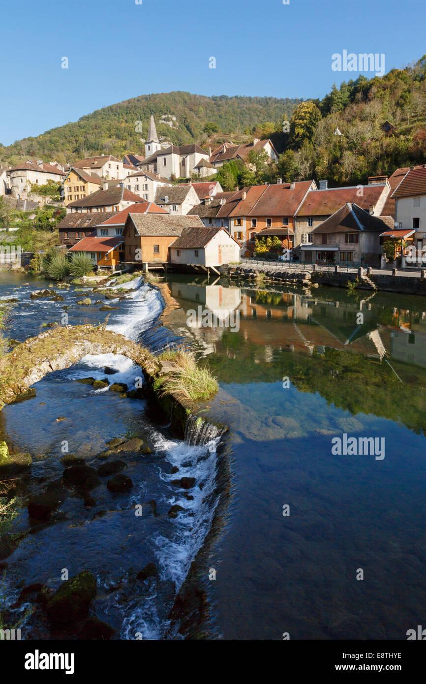 River Loue and medieval bridge in picturesque village one of Les Plus Beaux Villages de France. Lods, Loue Valley, - Stock Image