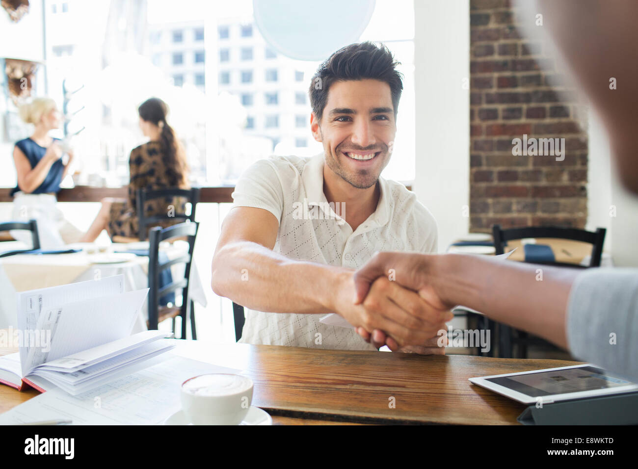 Businessmen shaking hands in cafe - Stock Image