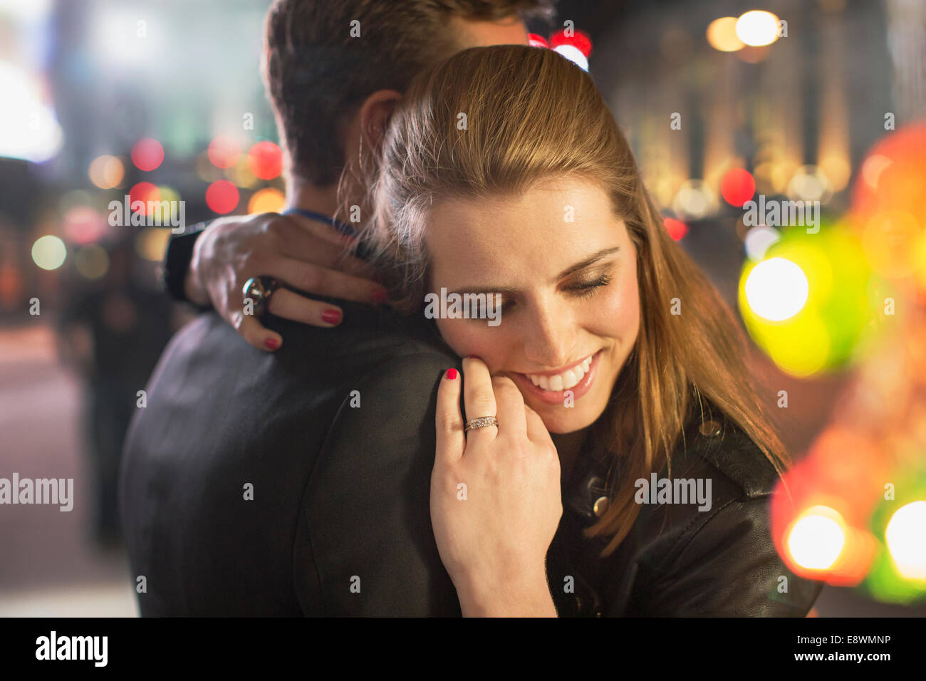 Couple hugging on city street at night - Stock Image