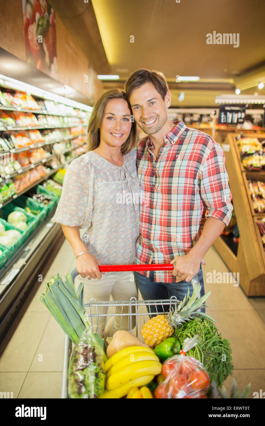 Couple Pushing Full Shopping Cart In Grocery Store Stock