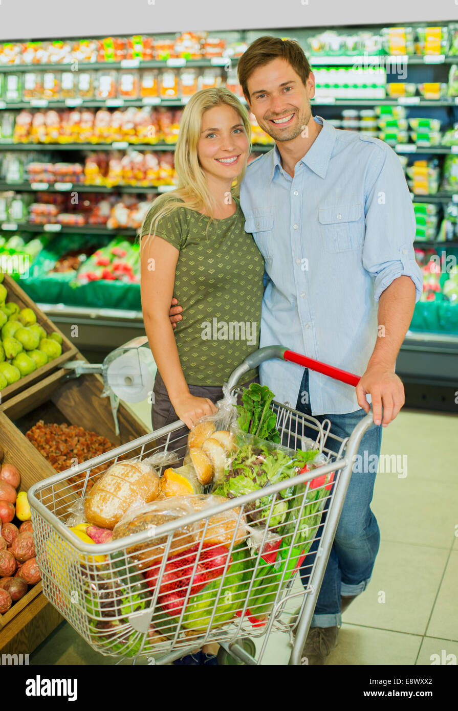 Couple Smiling With Full Shopping Cart In Grocery Store