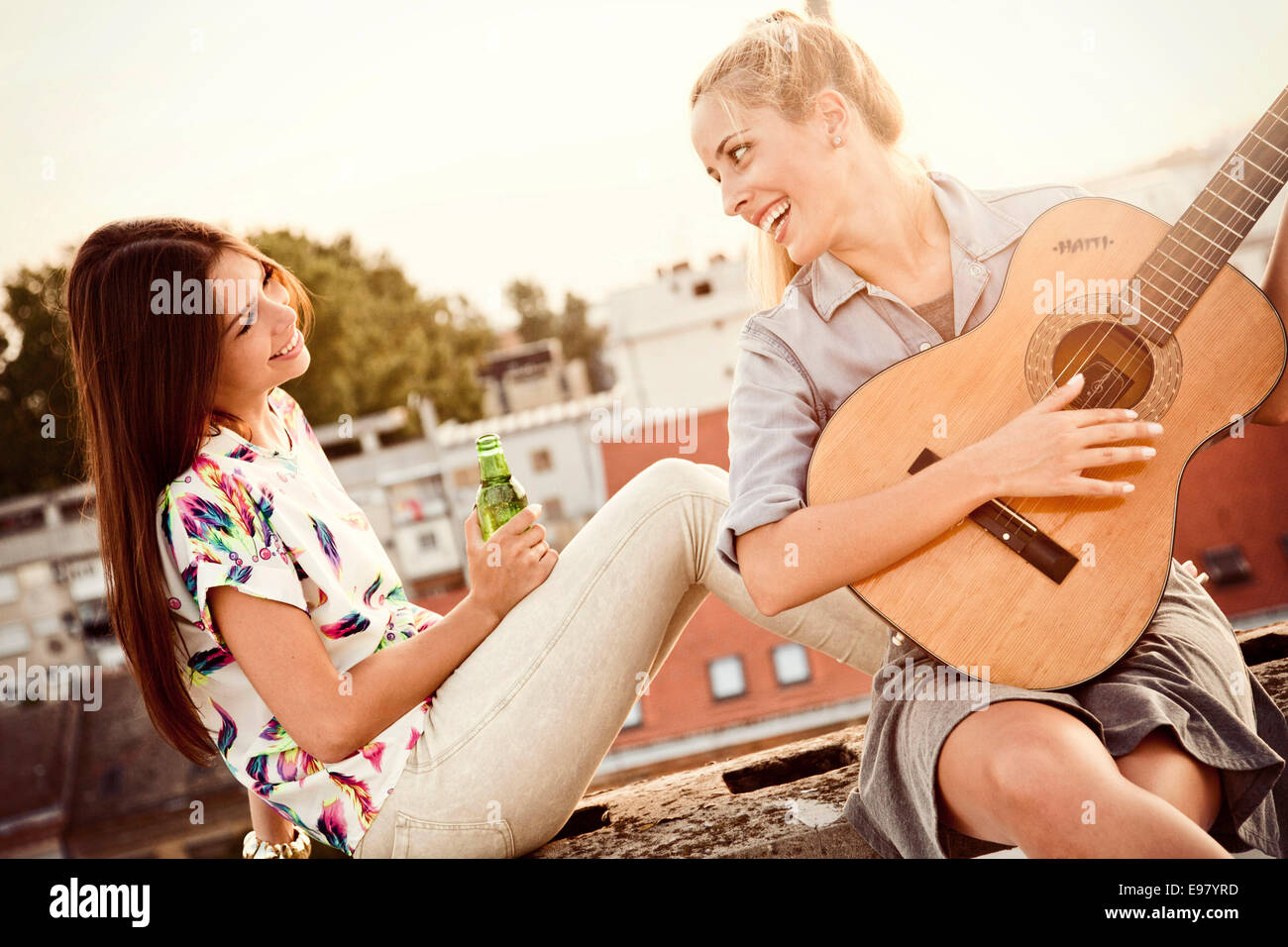 Young woman with girlfriend playing guitar at rooftop party - Stock Image