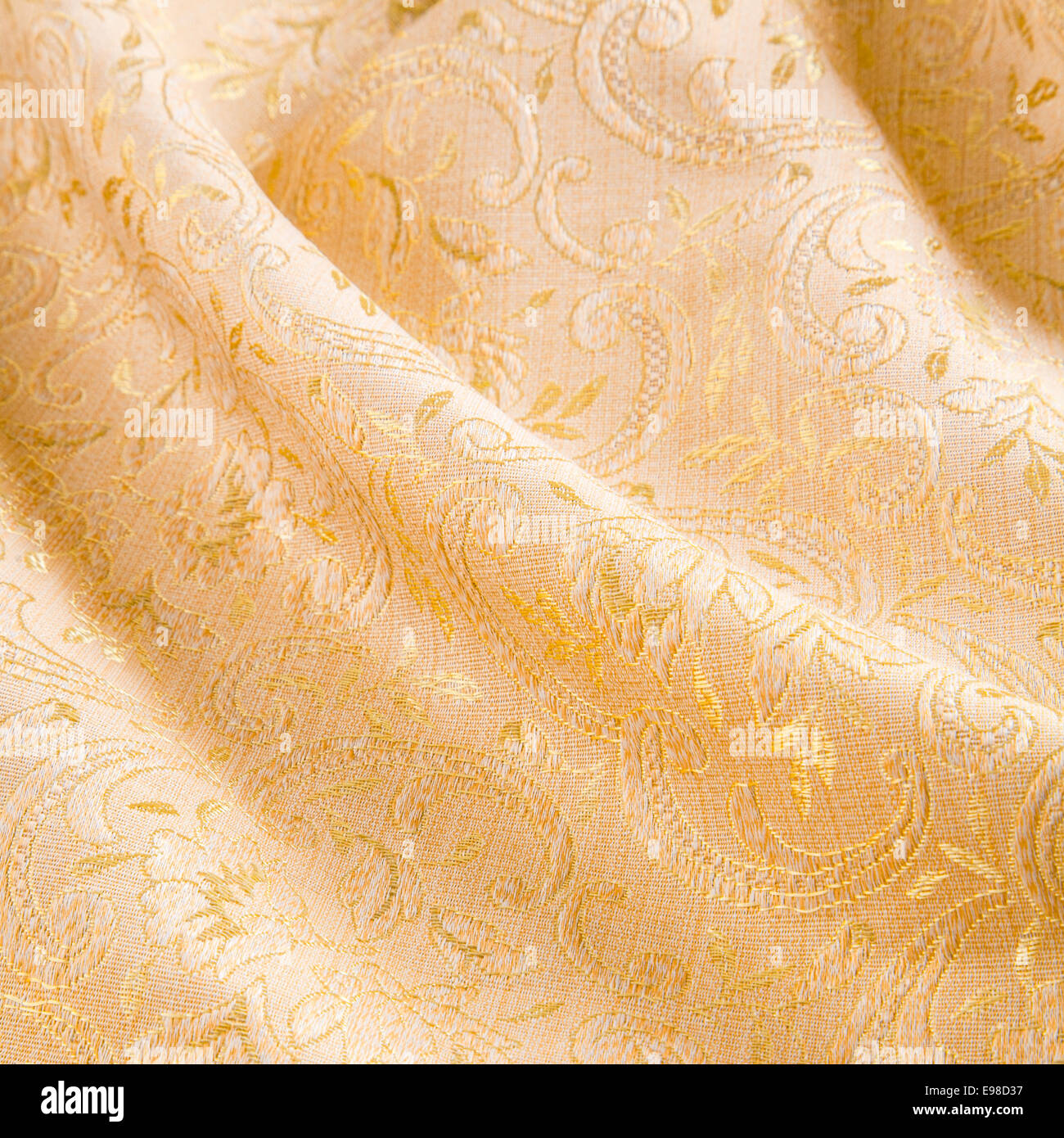 Luxurious gold damask fabric with a self pattern of acanthus leaves draped in an elegant diagonal manner with soft - Stock Image