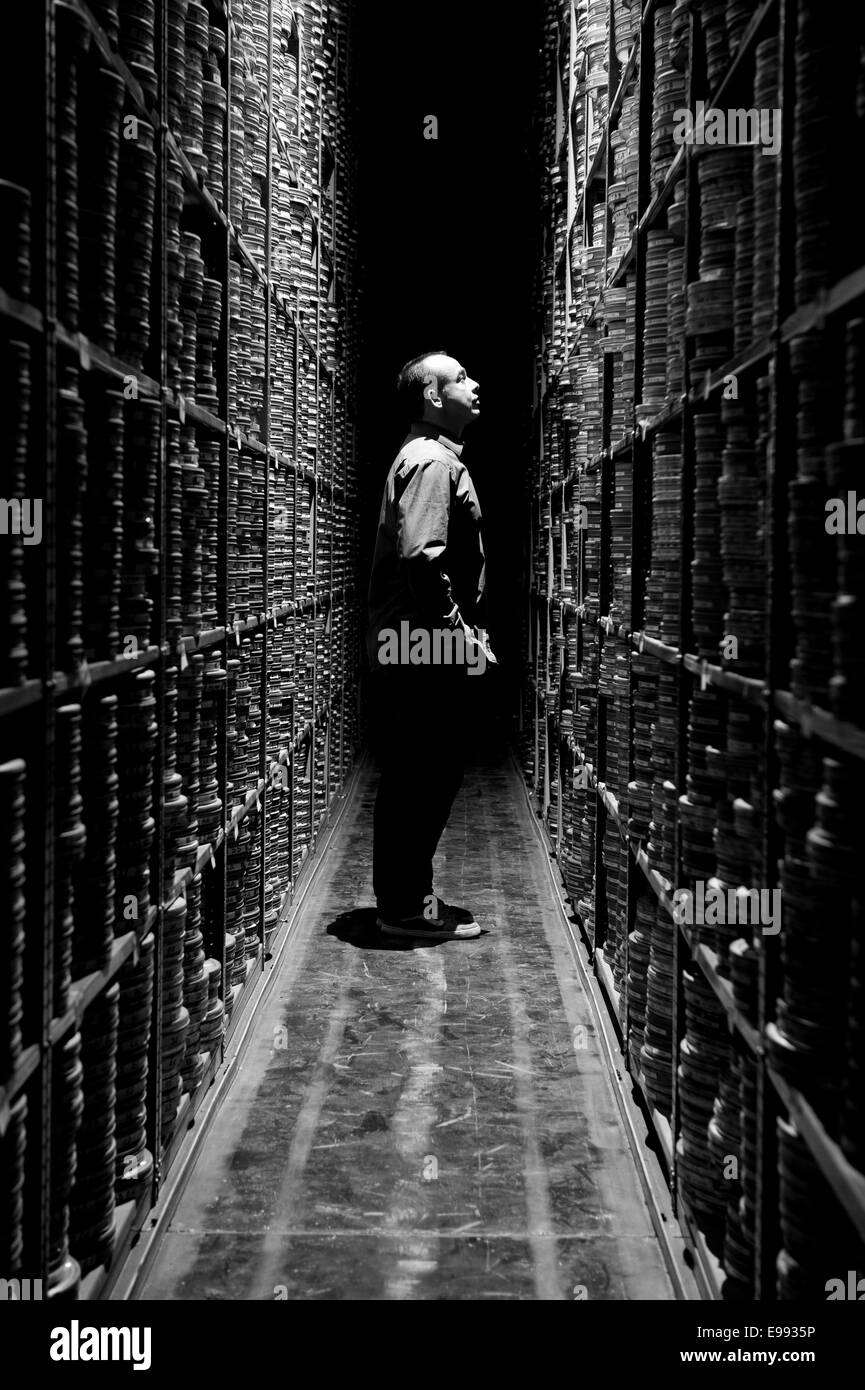 portrait of male member of staff at the BFI archive with storage shelves full of film reels / cartons housing classic - Stock Image