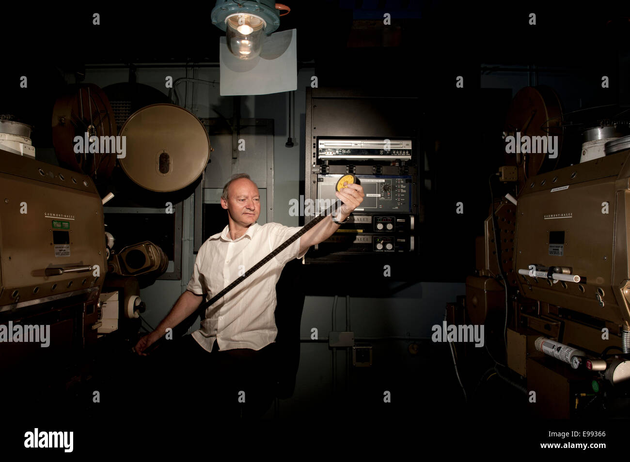 portrait of male member of staff at the BFI archive in the old cinema projection suite, looking at rolls of film - Stock Image