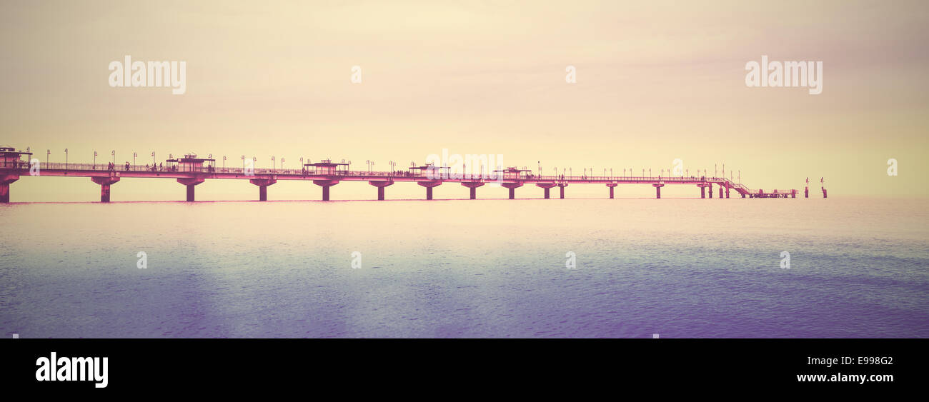 Retro filtered picture of long pier into the sea. - Stock Image
