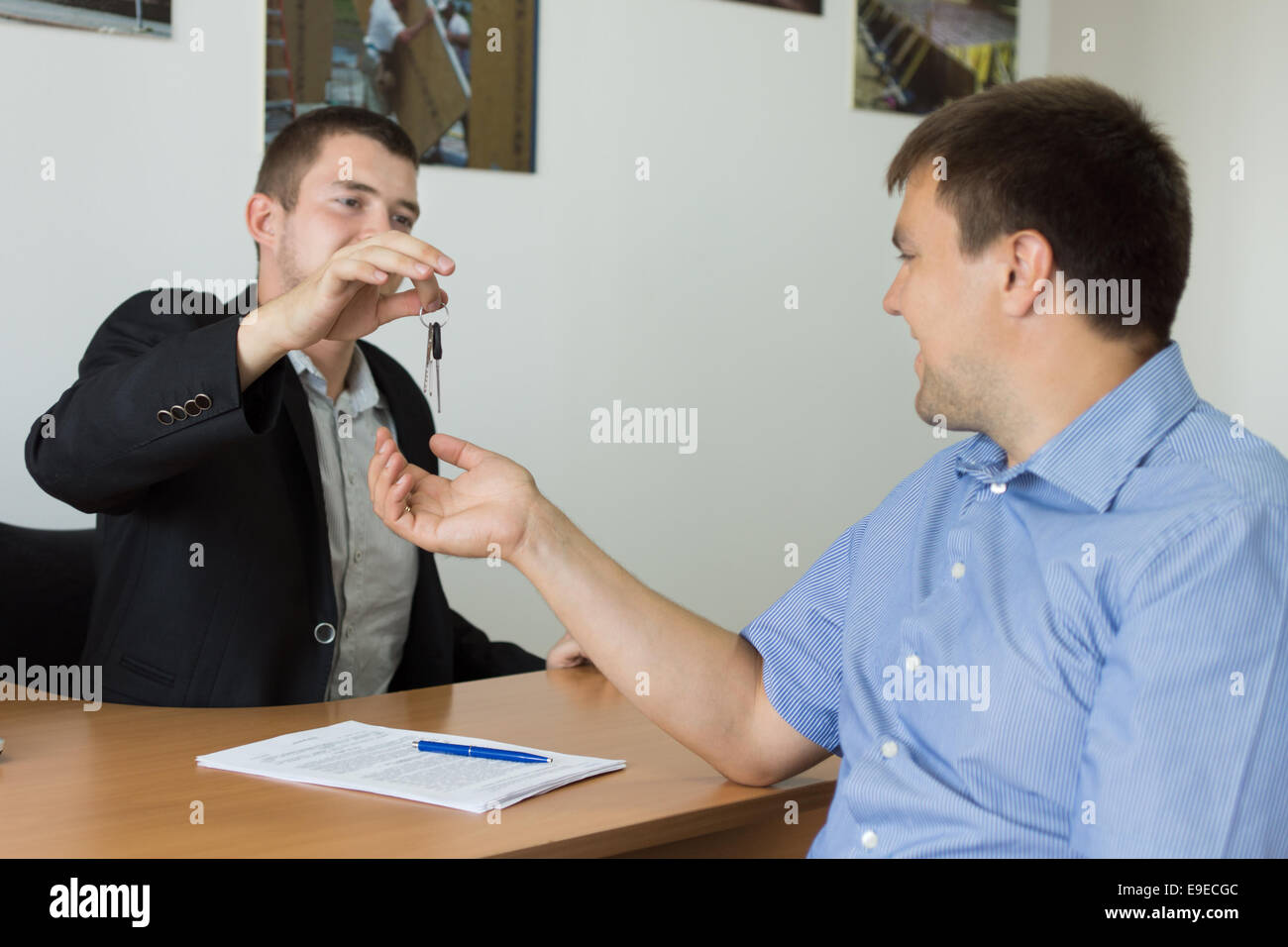 Estate agent or car salesman completing a deal and handing over the keys to the new purchaser in his office - Stock Image