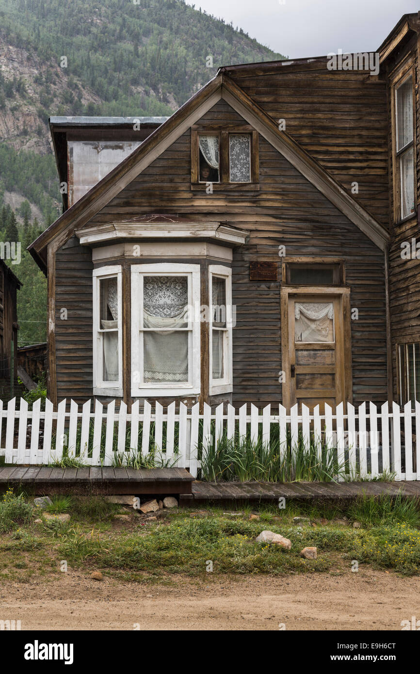 Old haunted house in the ghost town of St Elmo, Colorado, USA - with mannequin face at the window - Stock Image