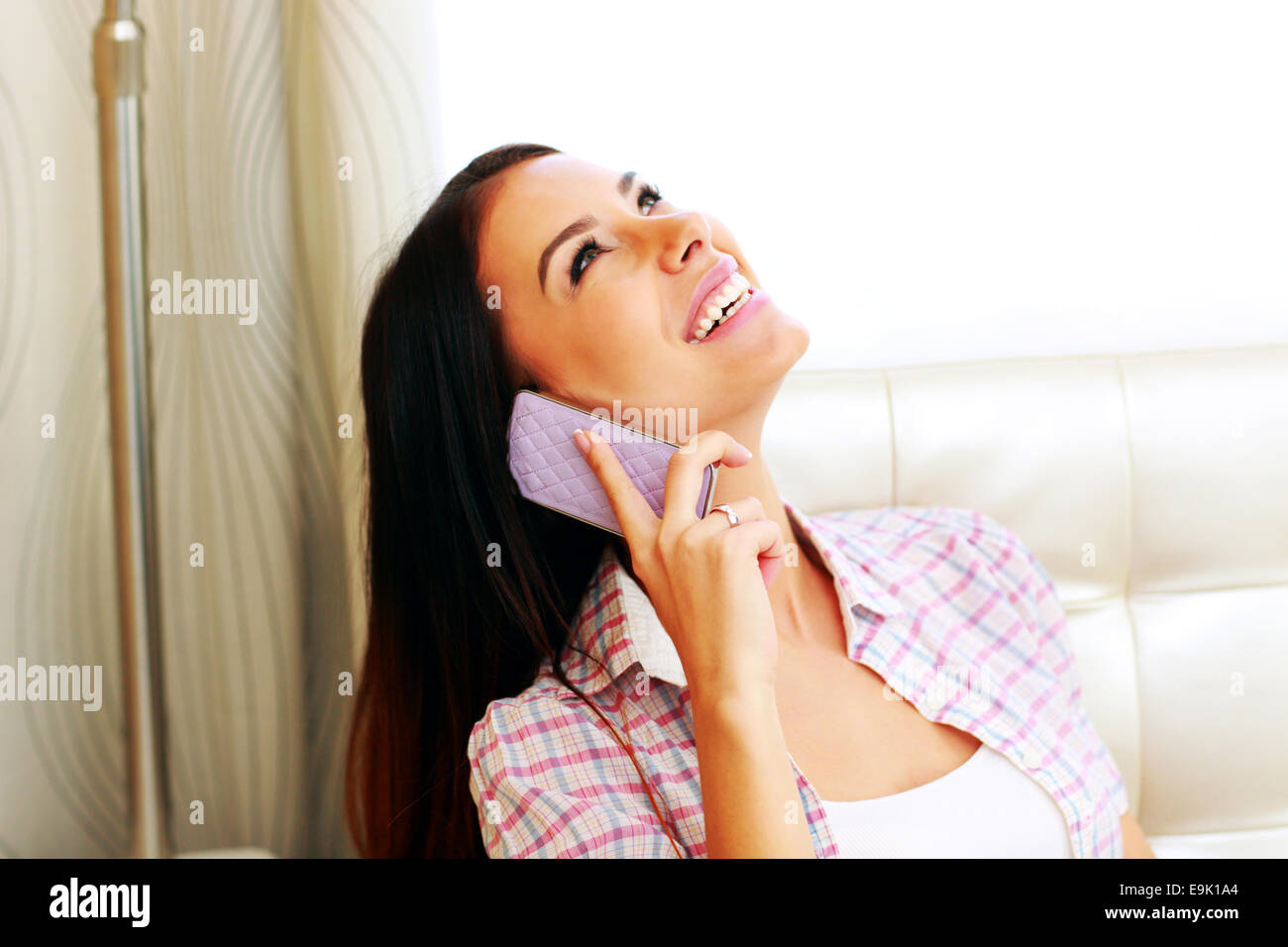 Happy young woman talking on the phone at home - Stock Image