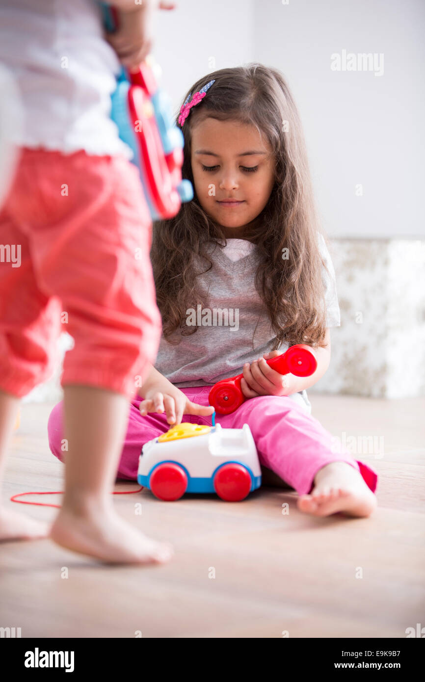 Cute girl dialing the toy telephone while playing with sister at home - Stock Image