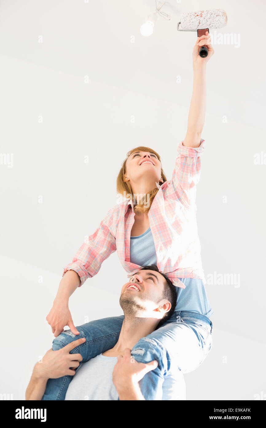 Woman on man's shoulders painting ceiling with paint roller - Stock Image