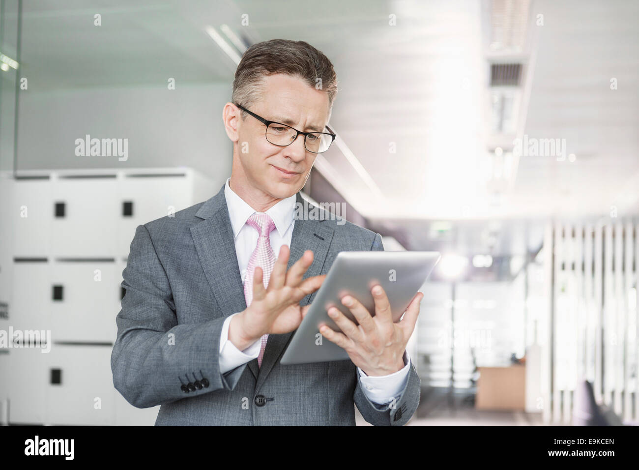 Young businesswoman using copy machine in office - Stock Image