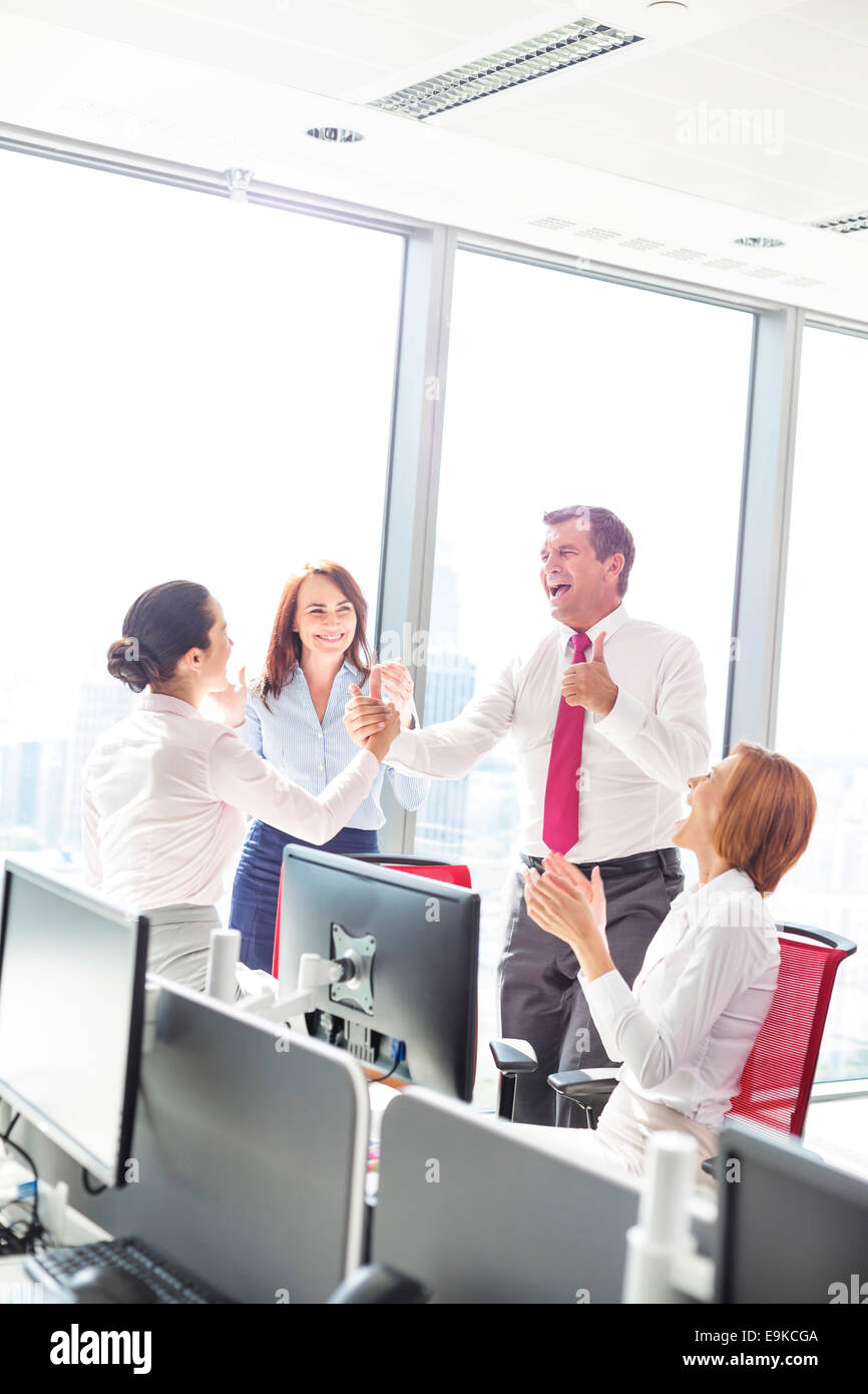 Businesspeople celebrating success in office - Stock Image