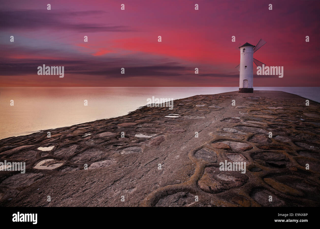 Lighthouse windmill with dramatic sunset sky. - Stock Image