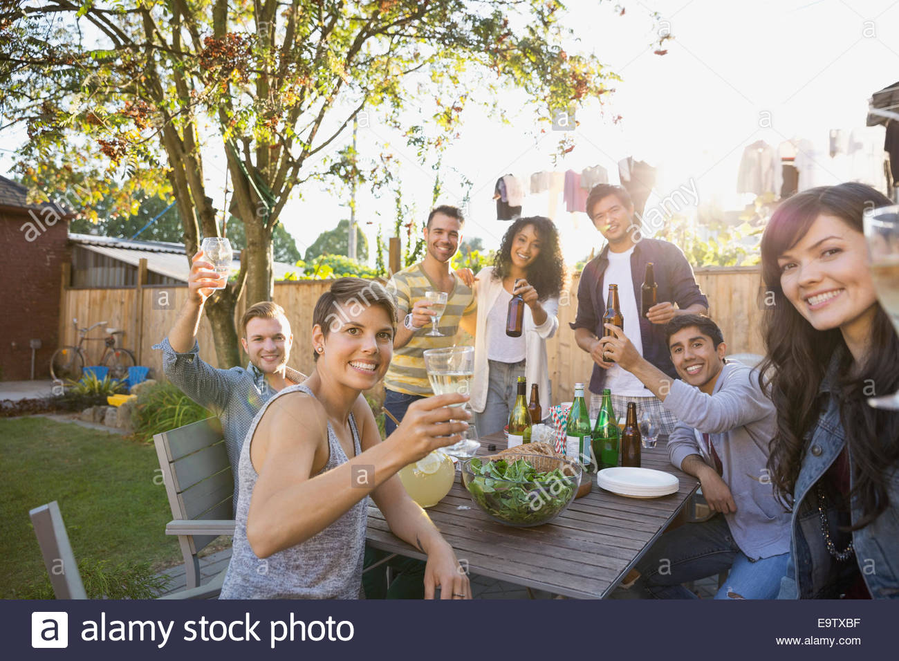 Portrait of friends toasting drinks at backyard barbecue - Stock Image