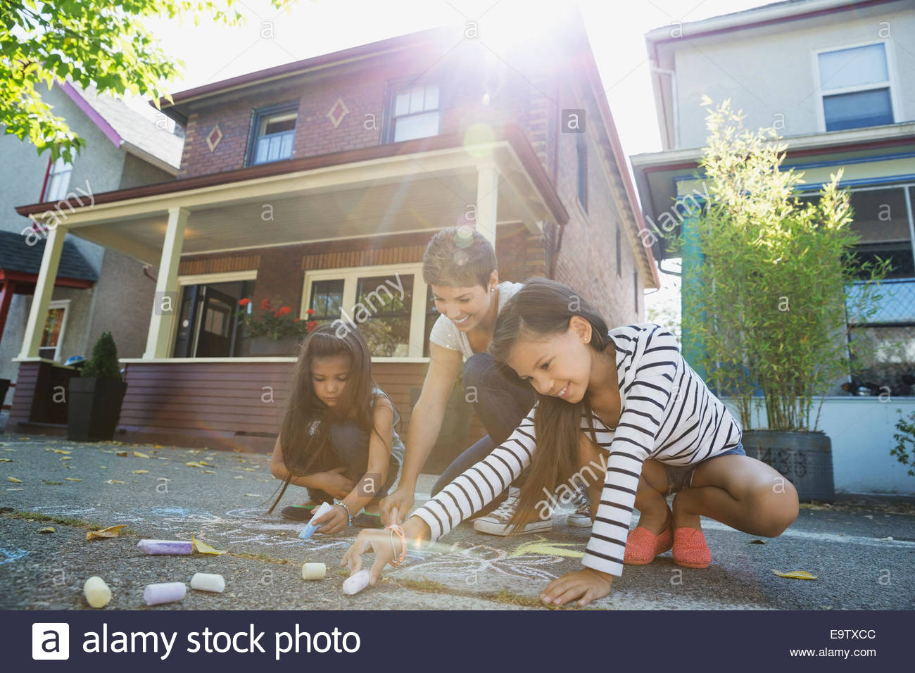 Mother and daughters drawing with sidewalk chalk - Stock Image