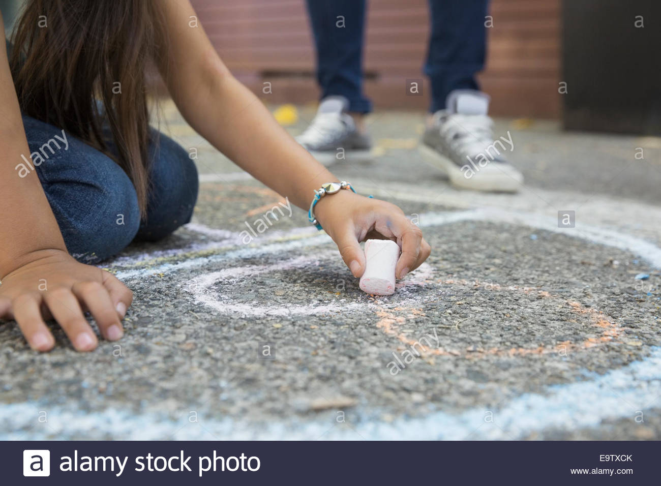 Girl drawing hopscotch number 8 with sidewalk chalk - Stock Image