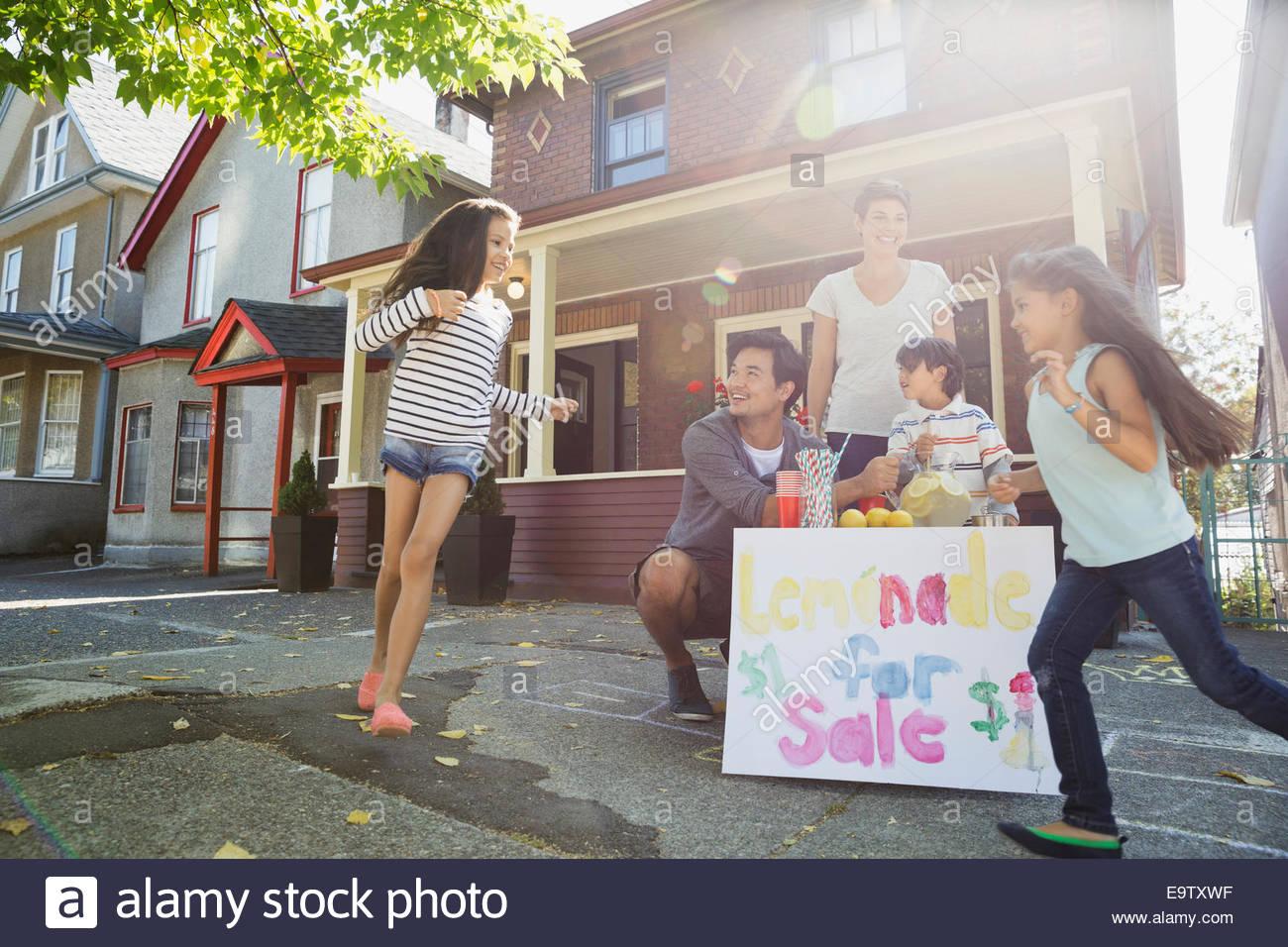 Family at lemonade stand on sidewalk outside house - Stock Image