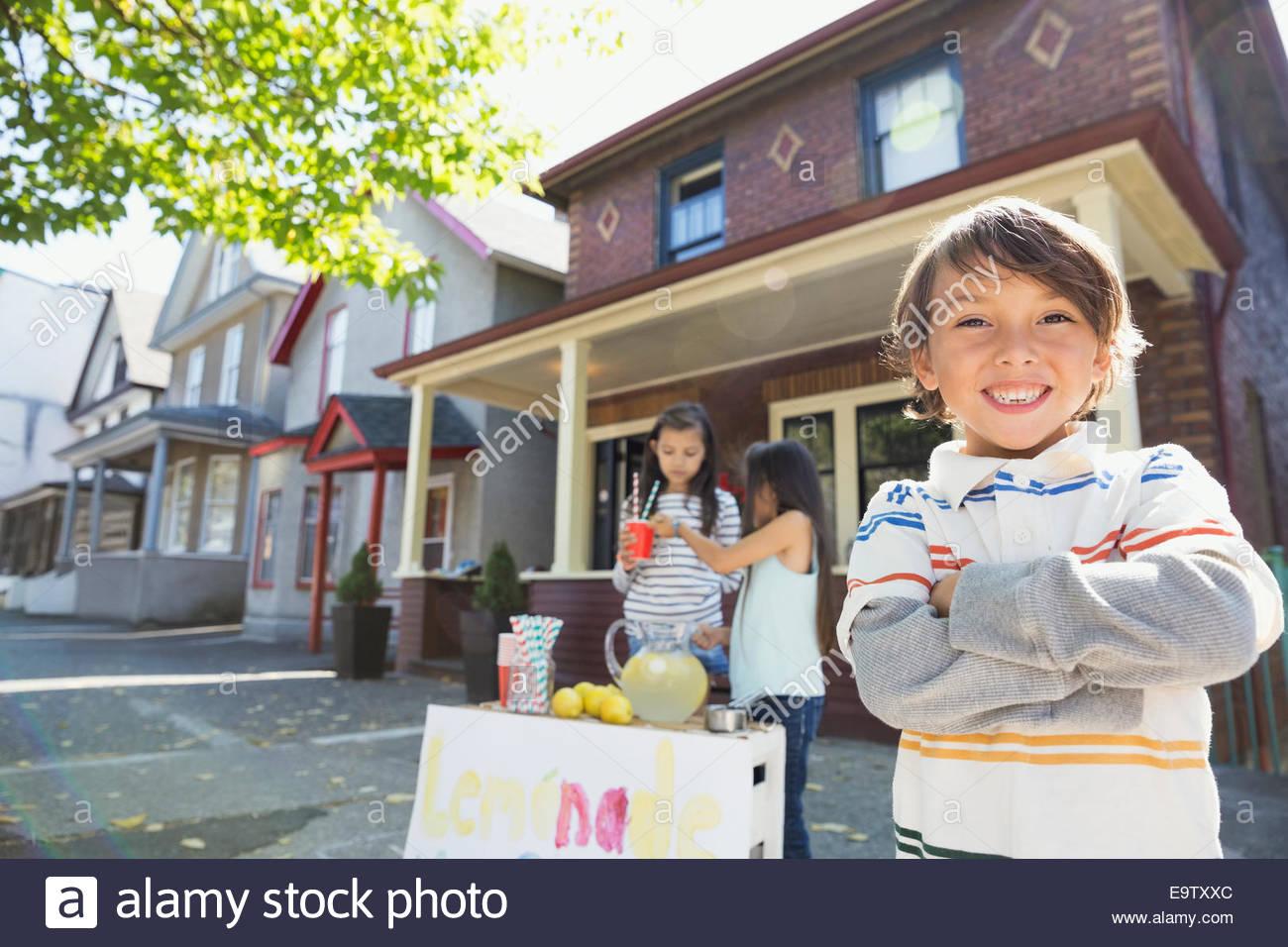 Portrait of confident boy at lemonade stand - Stock Image