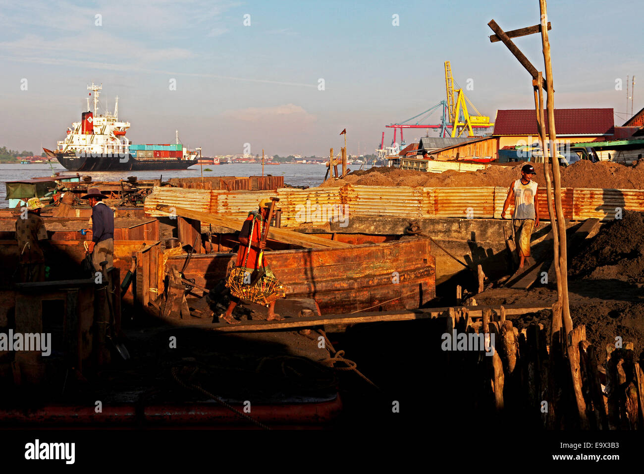 Workers uploading sands from a barge while a cargo ship passes through the Musi River in South Sumatra, Indonesia. - Stock Image