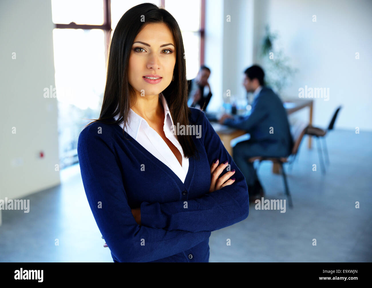 Beautiful woman standing with arms folded with colleagues on background - Stock Image