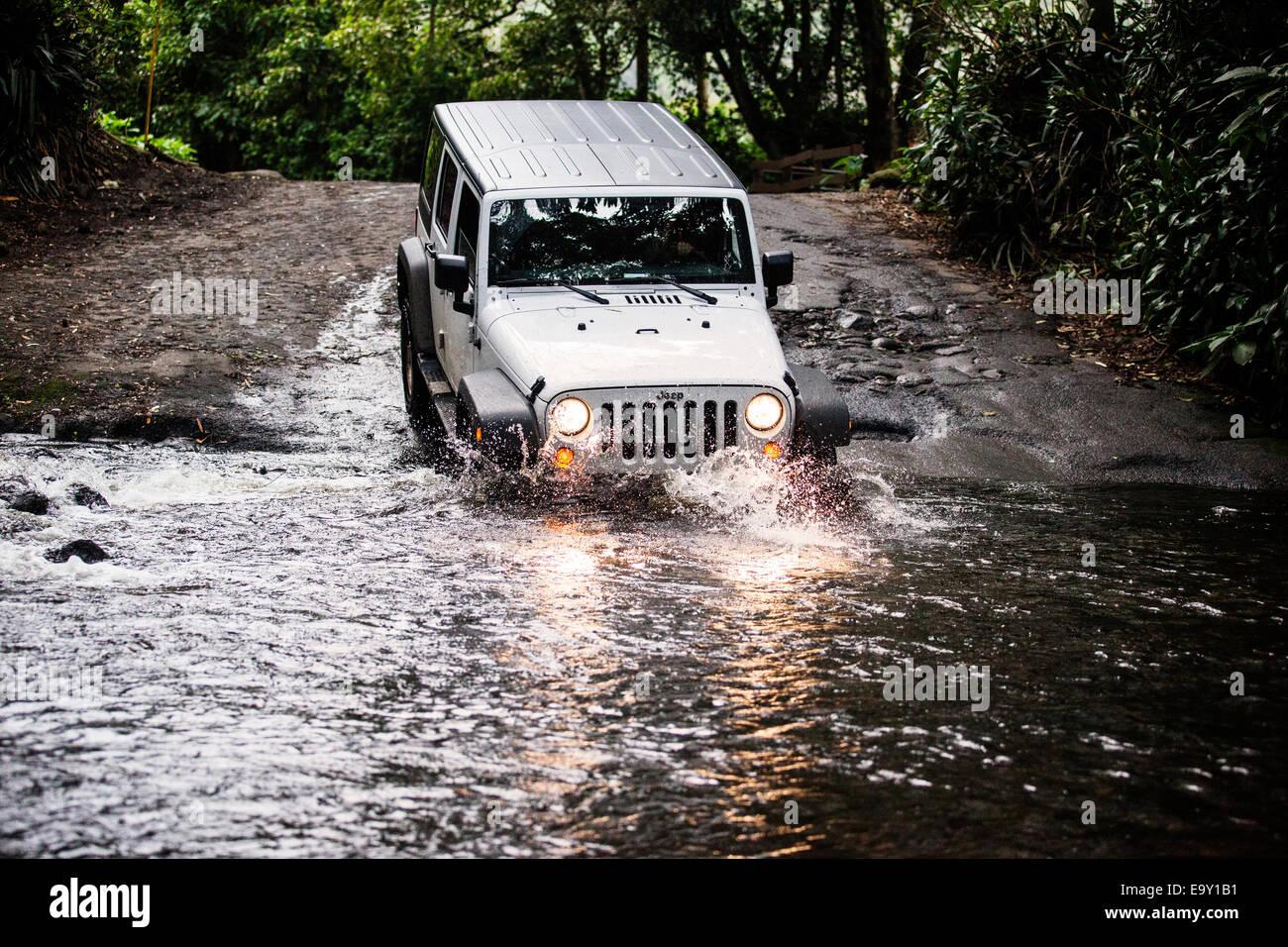 Jeep crossing a stream in Waipio Valley, Big Island, Hawaii, United States - Stock Image
