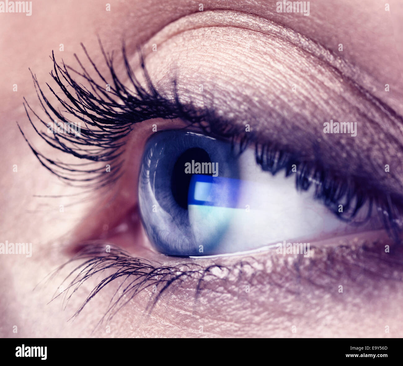Closeup of a young woman eye with blue computer screen reflection in it - Stock Image