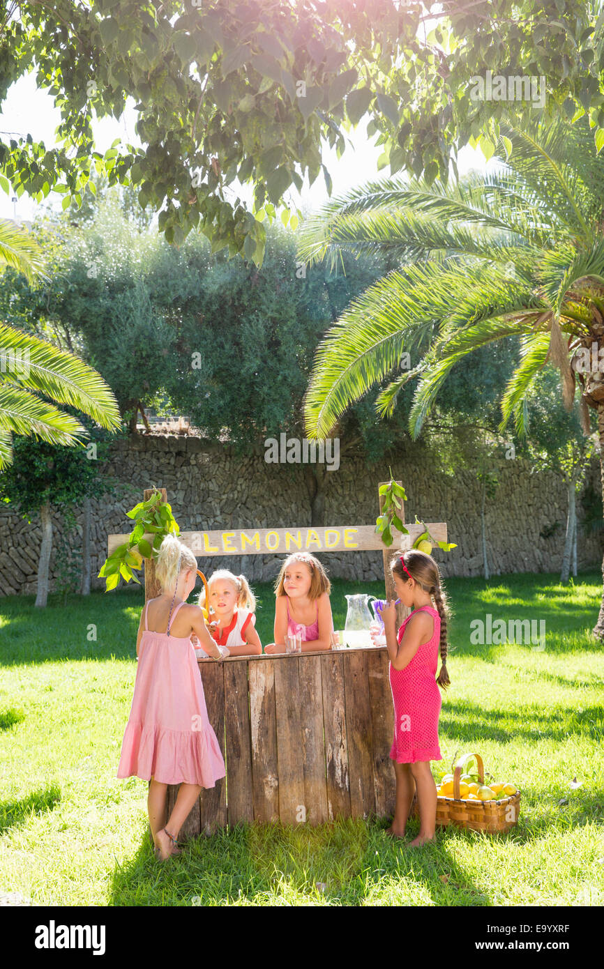 Four girls chatting at lemonade stand in park - Stock Image