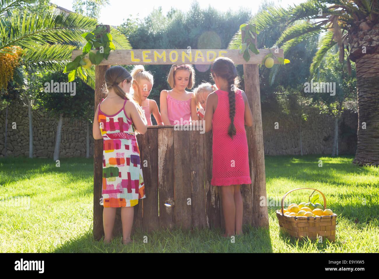 Five girls buying and selling fresh lemonade at lemonade stand in park - Stock Image
