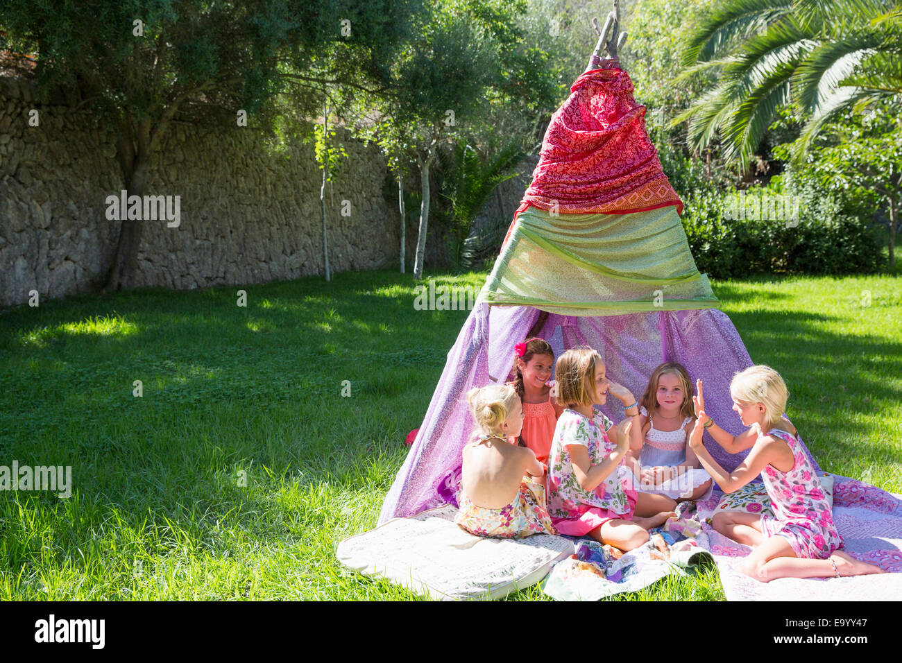 Five girls playing clapping games in front of teepee - Stock Image